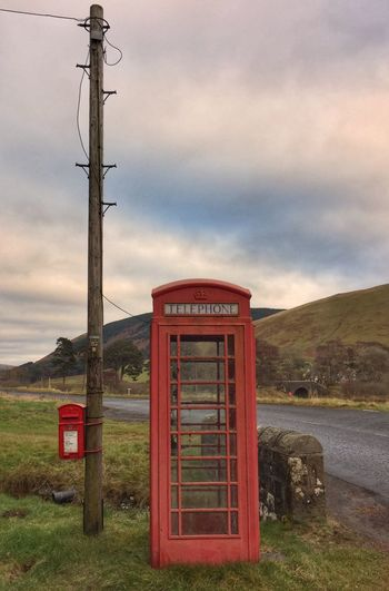 Telephone box and post box Red Communication Telephone Booth Sky Cloud - Sky Built Structure Outdoors No People Day Nature Mountain Grass Architecture Landscape