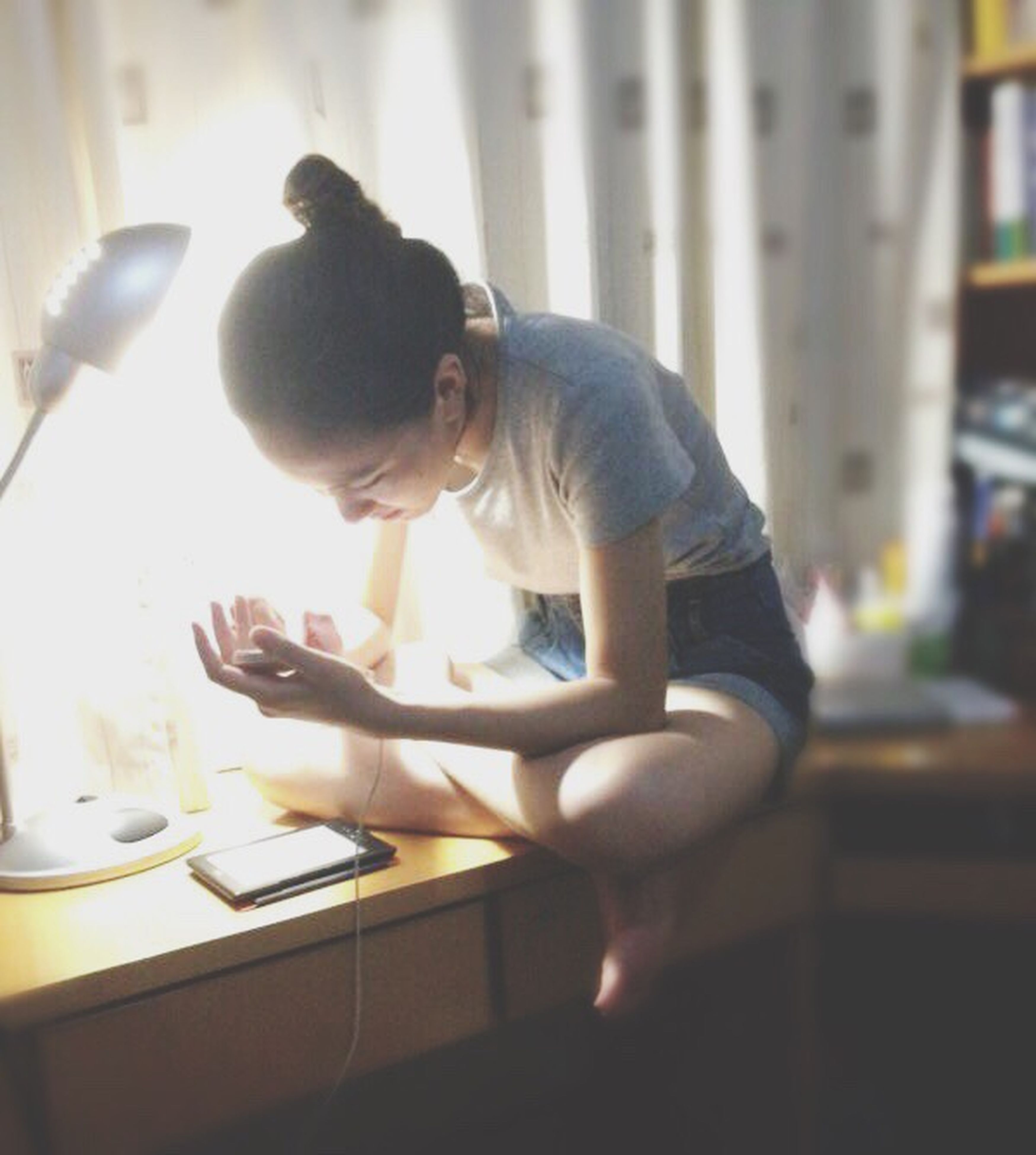 indoors, childhood, home interior, sitting, lifestyles, leisure activity, person, elementary age, table, girls, illuminated, playing, glass - material, home, casual clothing, domestic room, window, holding
