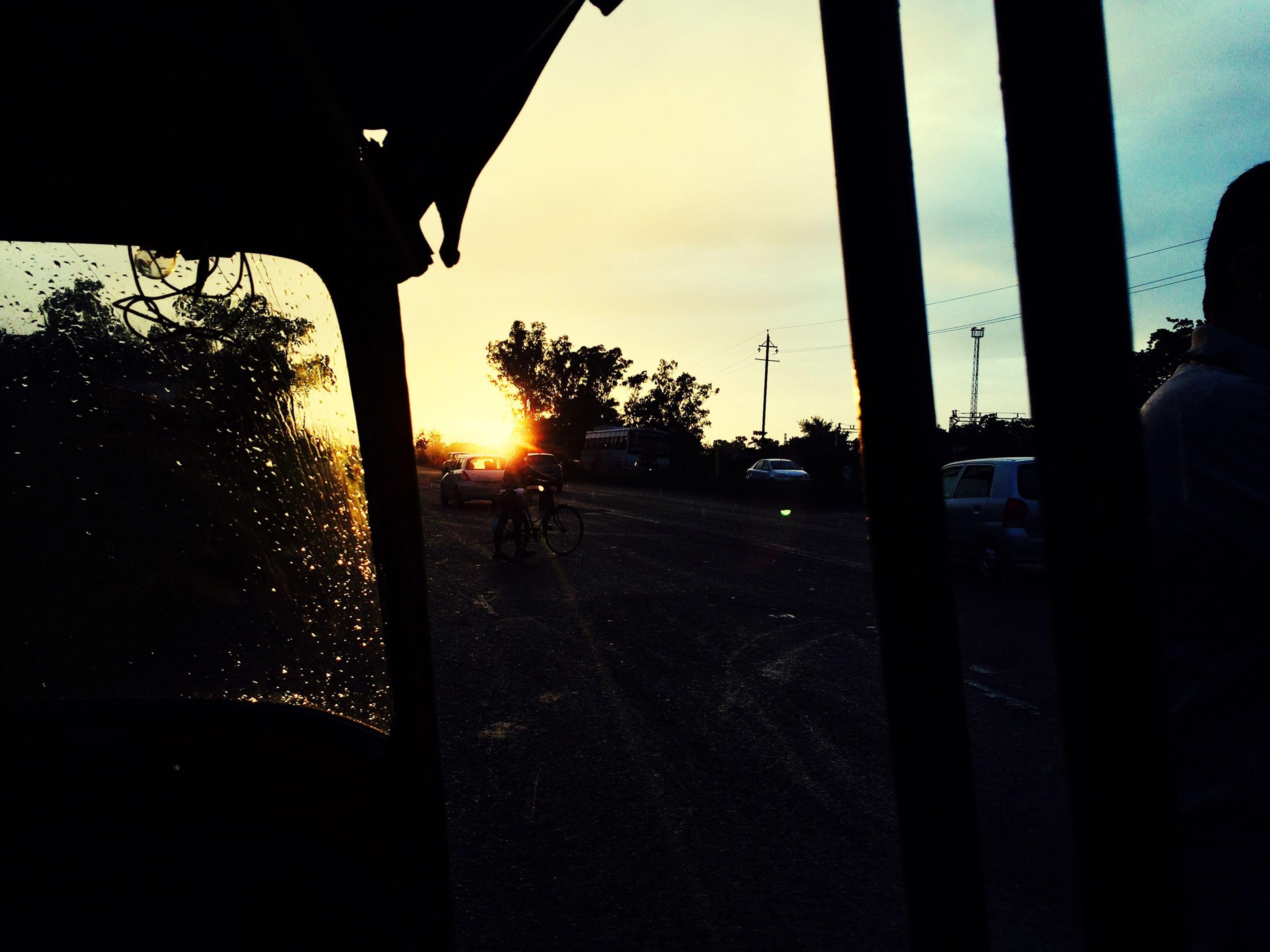 sunset, silhouette, sun, tree, sky, sunlight, sunbeam, transportation, lens flare, car, street, orange color, road, back lit, land vehicle, built structure, dark, cloud - sky, nature, street light