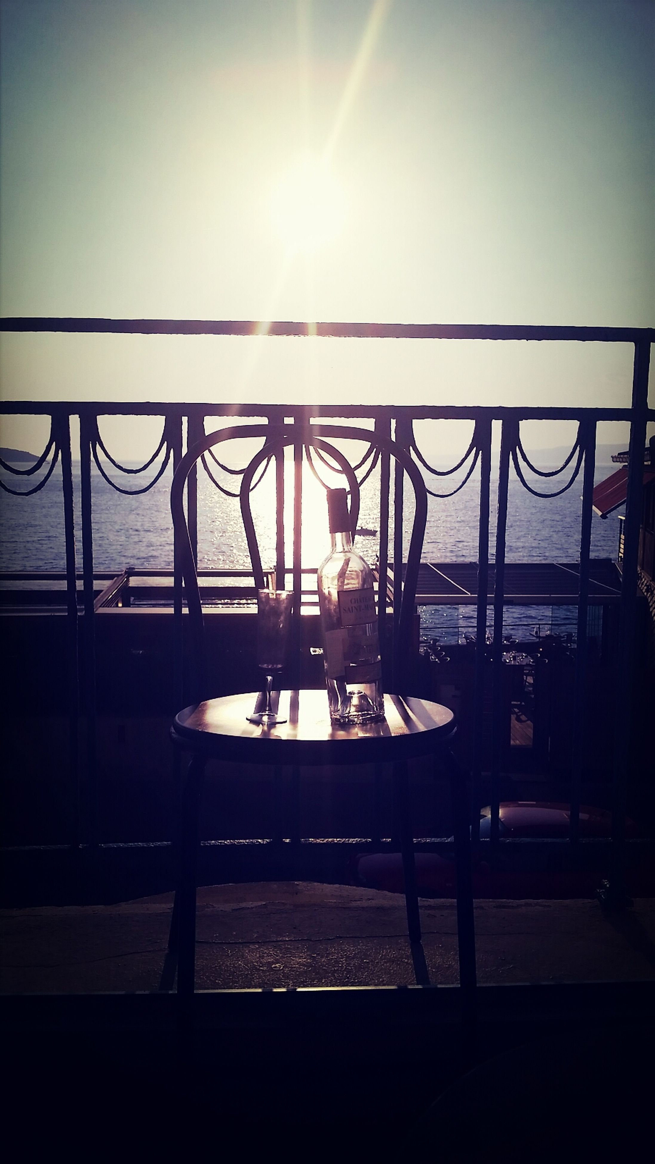 silhouette, sunlight, sun, railing, built structure, sunset, sea, chair, clear sky, sunbeam, architecture, sky, water, indoors, copy space, incidental people, lens flare, table, empty