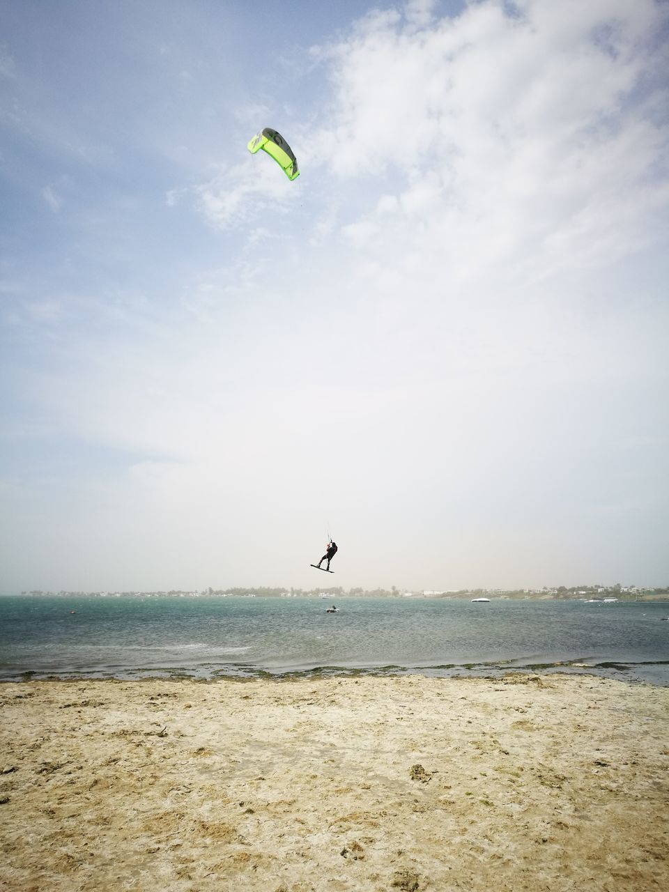 sea, flying, mid-air, sky, horizon over water, beach, water, day, nature, outdoors, tranquil scene, scenics, leisure activity, one person, parachute, beauty in nature, cloud - sky, summer, tranquility, vacations, real people, adventure, extreme sports, sport, bird, animal themes, paragliding, people