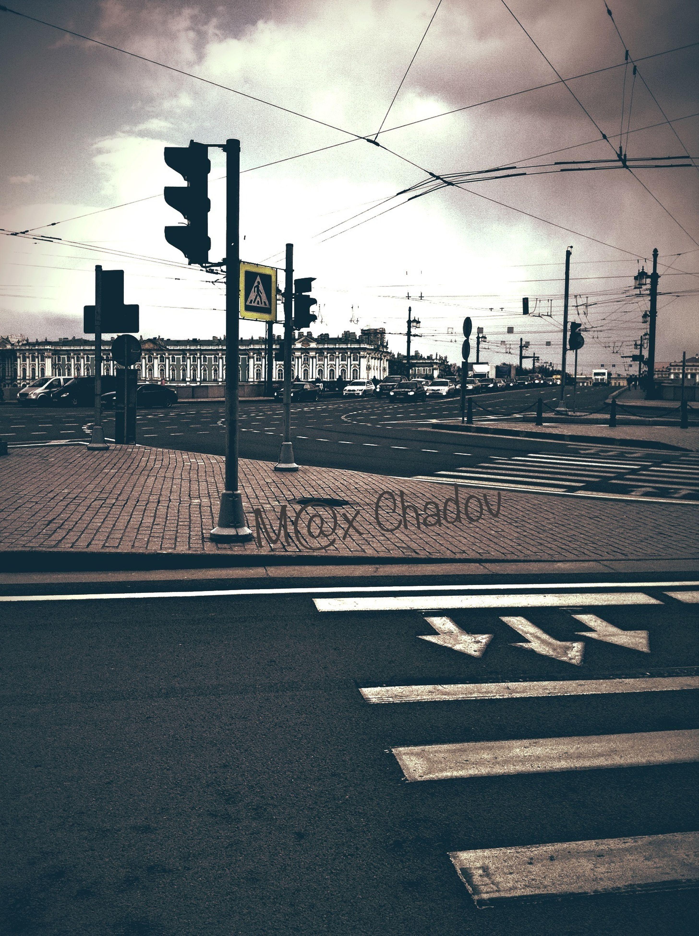 road marking, sky, street, built structure, architecture, building exterior, road, city, transportation, communication, cloud - sky, sunset, street light, sunlight, text, outdoors, city life, guidance, arrow symbol, shadow