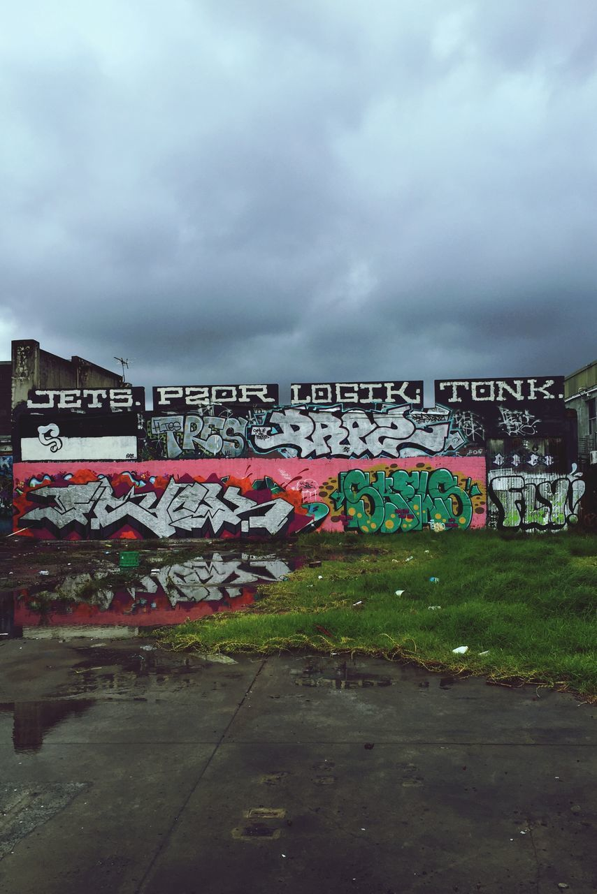 cloud - sky, text, graffiti, sky, architecture, outdoors, built structure, communication, day, building exterior, multi colored, no people, nature