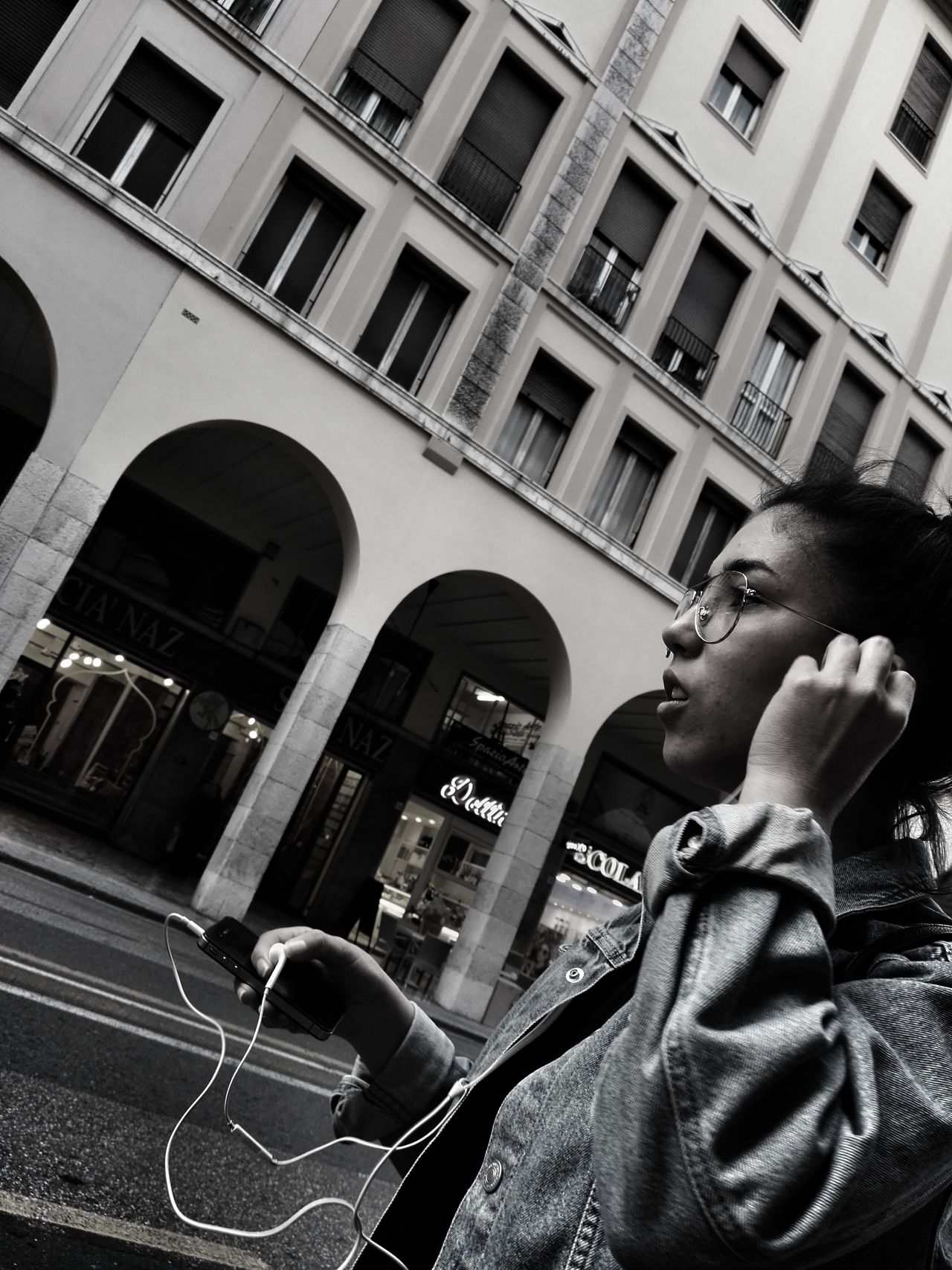 Low Angle View One Person Architecture Lifestyles Built Structure Building Exterior Real People People Adult Women Girl Street Photography Black And White Model Casual Clothing City Life City Street Bianco E Nero Ragazza EyeEm Gallery EyeEm Best Shots Listen To Music Music Listening Music The Street Photographer - 2017 EyeEm Awards