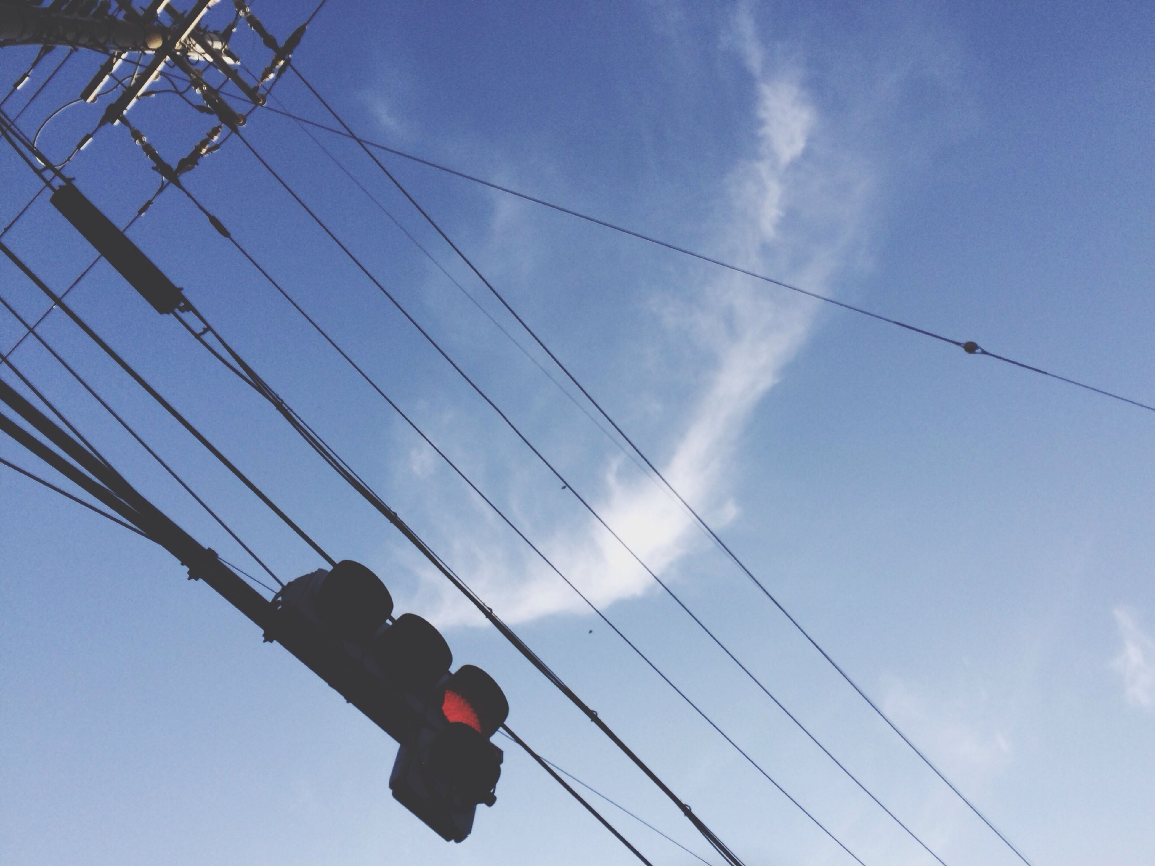 low angle view, cable, power line, sky, connection, electricity, technology, power supply, cloud - sky, leisure activity, electricity pylon, blue, lifestyles, men, power cable, transportation, day, cloud