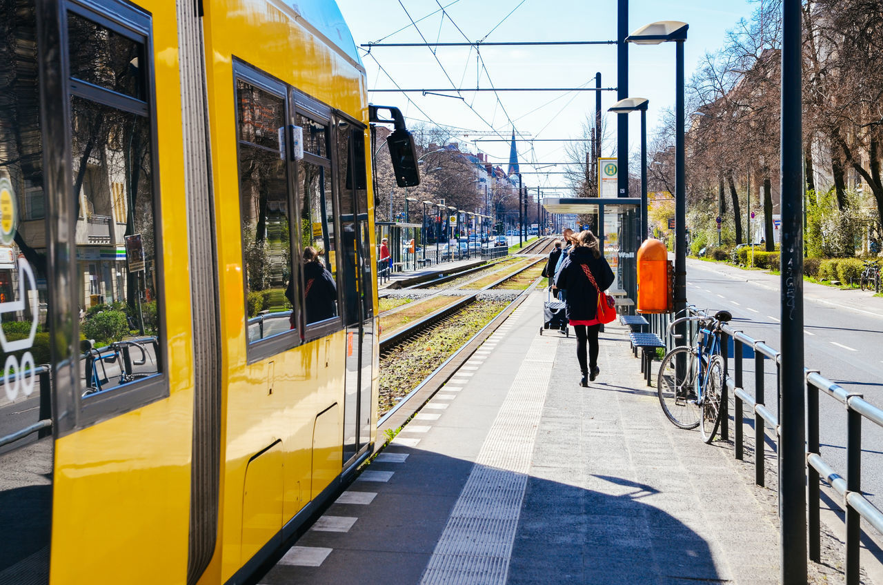 YELLOW TRAM AT STATION IN A SUNNY DAY