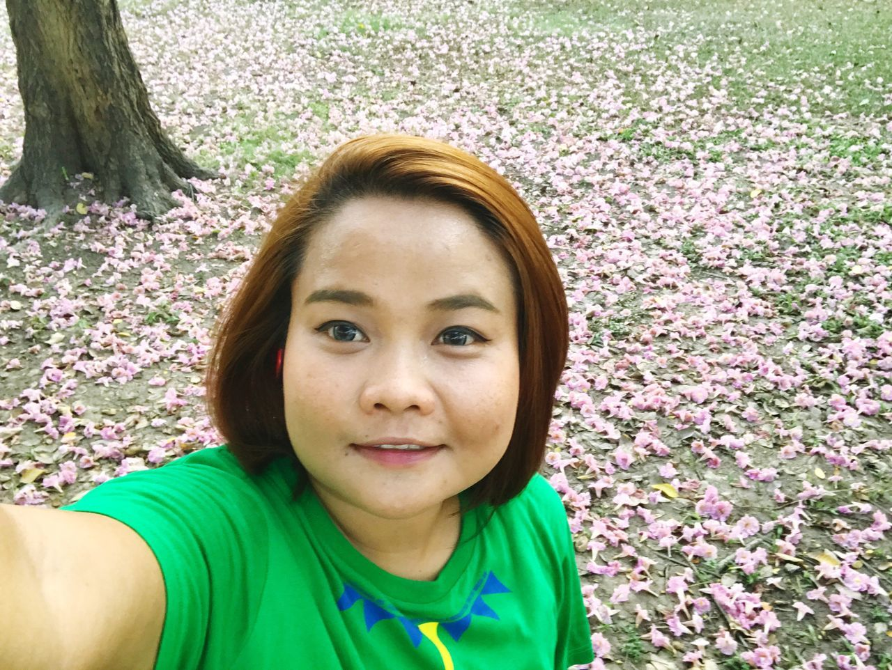 looking at camera, portrait, real people, front view, day, one person, flower, outdoors, park - man made space, casual clothing, smiling, leisure activity, headshot, tree, lifestyles, nature, happiness, young women, young adult, close-up, people
