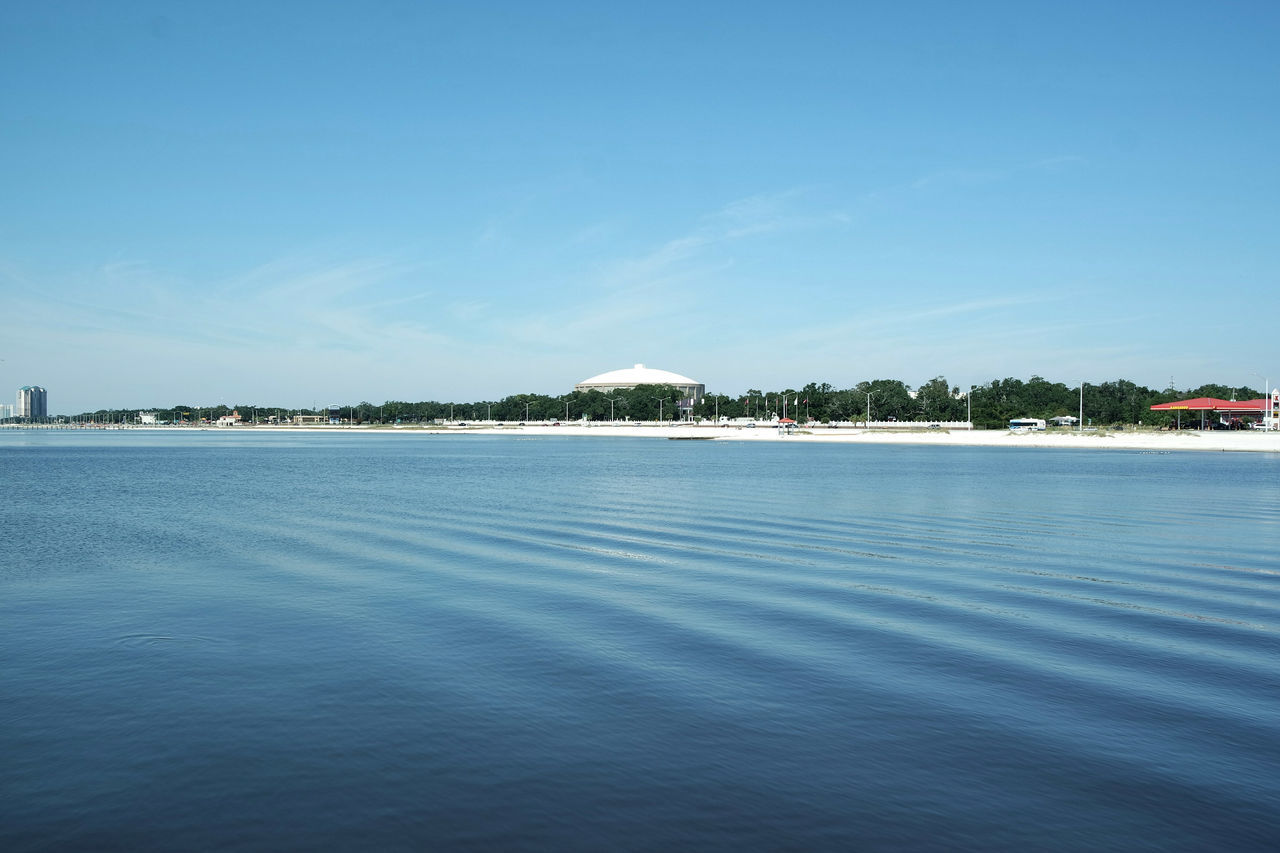 water, tranquil scene, blue, sea, waterfront, sky, tranquility, outdoors, scenics, day, rippled, beauty in nature, no people, nature, architecture, built structure, building exterior, view into land, nautical vessel, clear sky