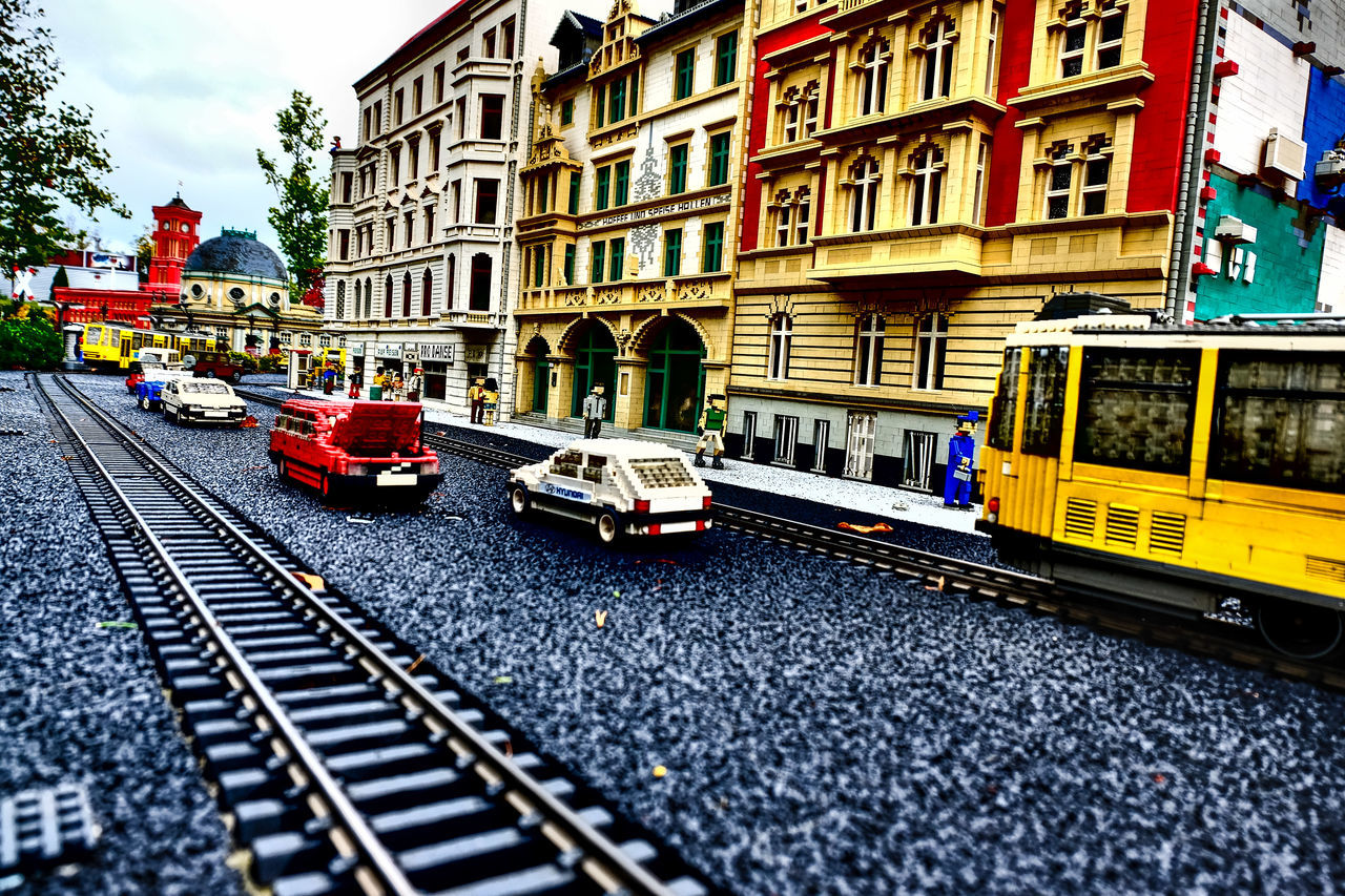transportation, architecture, building exterior, mode of transport, built structure, day, land vehicle, public transportation, outdoors, railroad track, city, no people, sky
