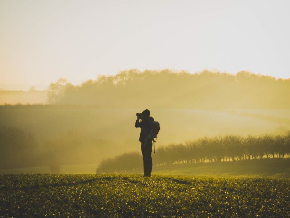 Photography Themes Standing Photographing Camera - Photographic Equipment Landscape Nature Field Full Length Nature_collection One Person Real People Men Holding Outdoors Sky Grass Beauty In Nature Digital Camera Tree Photographer Countryside Leisure Activity Foggy Hazy  EyeEm Best Shots