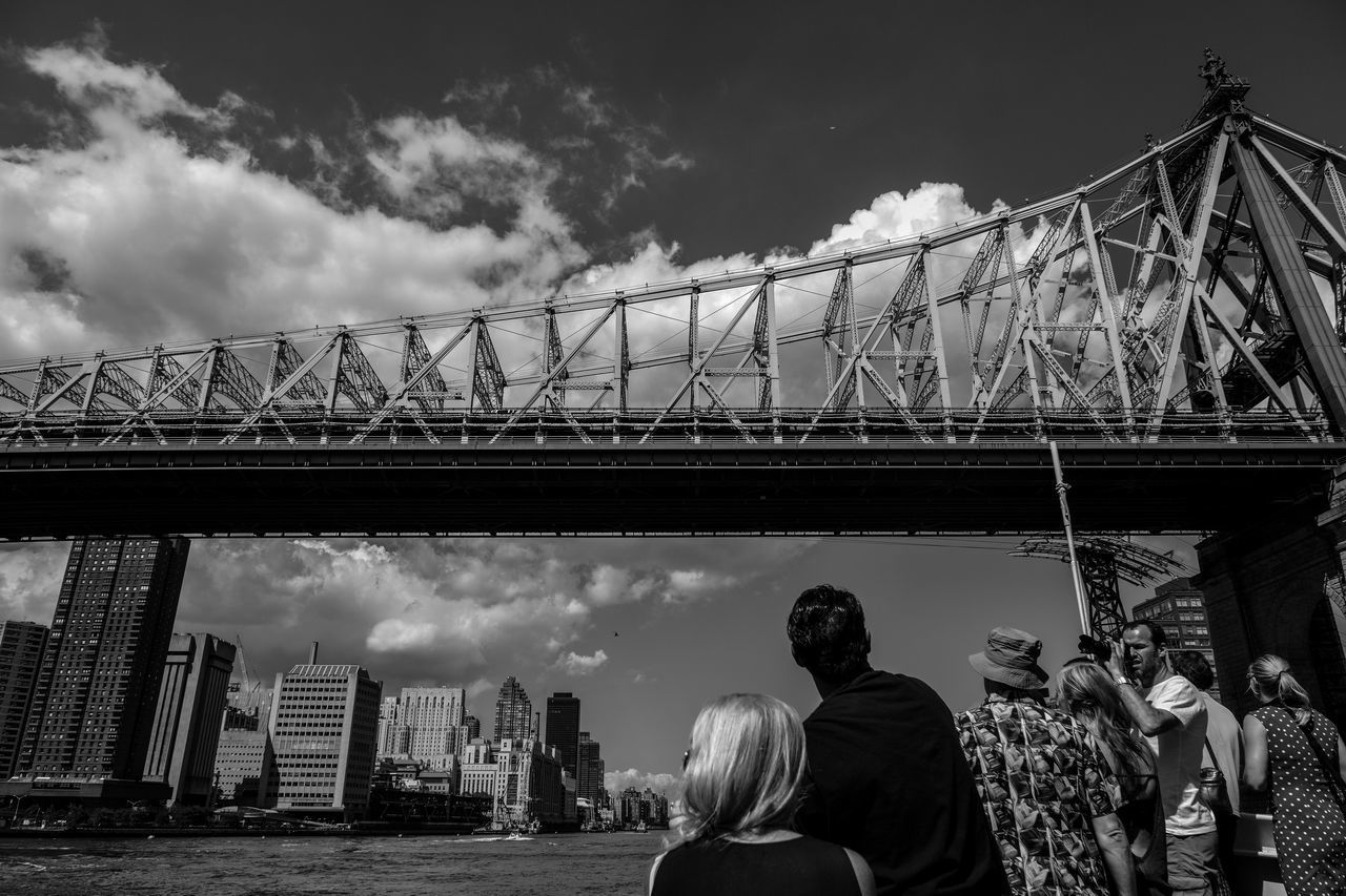 bridge - man made structure, real people, connection, sky, built structure, cloud - sky, architecture, men, women, lifestyles, transportation, leisure activity, rear view, large group of people, day, outdoors, low angle view, suspension bridge, bridge, city, people