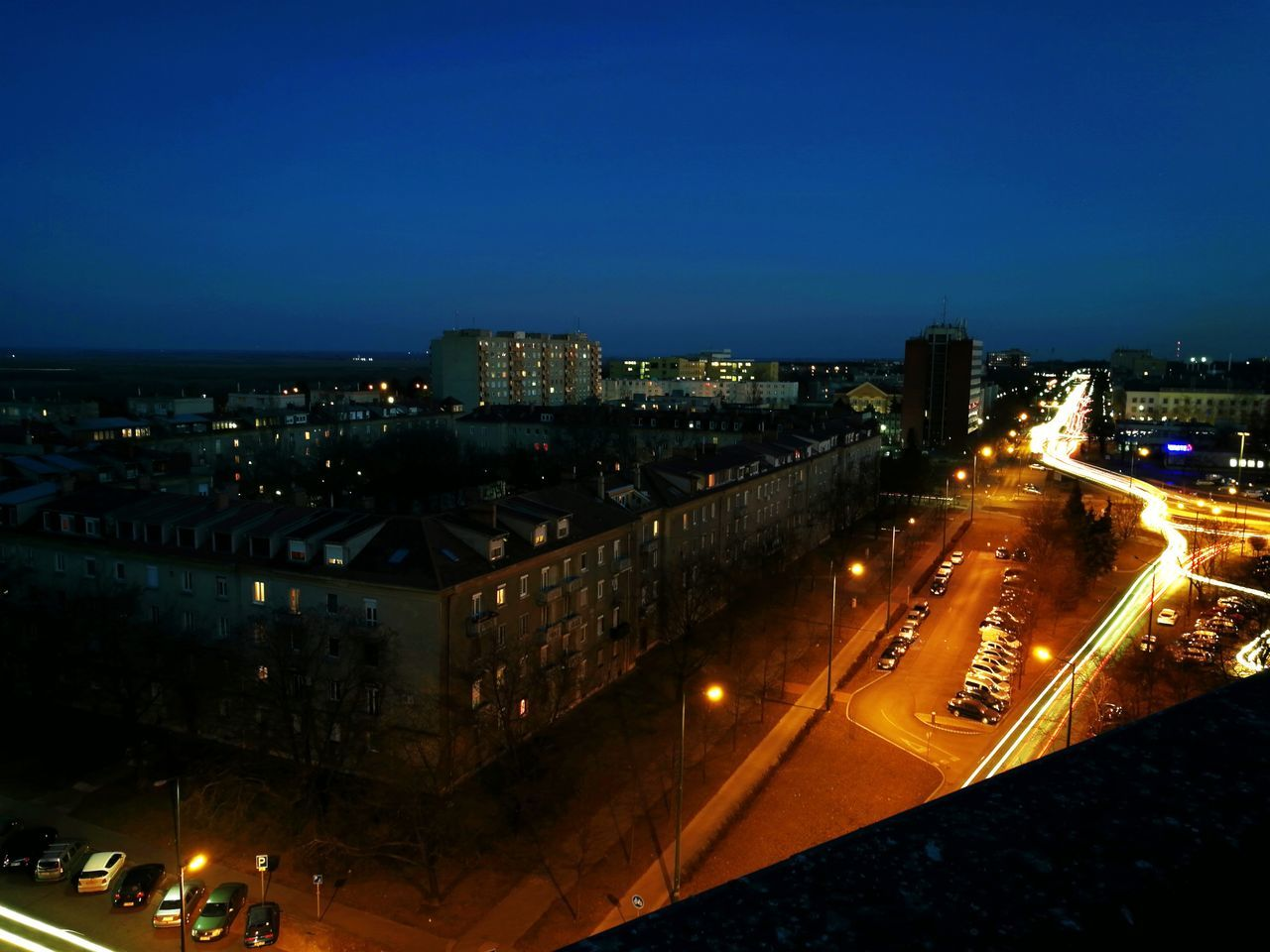 illuminated, architecture, building exterior, city, night, built structure, cityscape, high angle view, transportation, outdoors, city life, road, blue, no people, sky, clear sky, skyscraper, high street