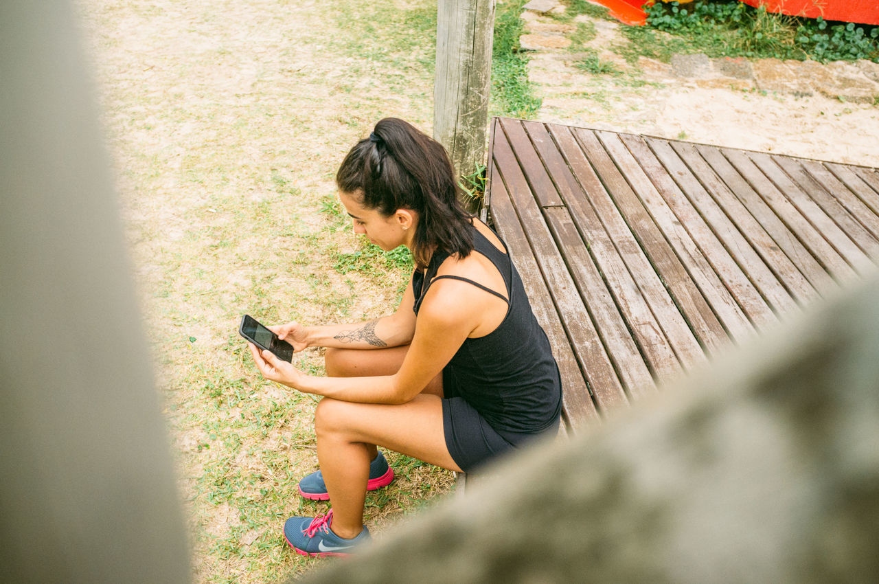 Adult Beach Brazil Communication Day Florianópolis Full Length Leisure Activity Lifestyles Mobile Phone Nature One Person Outdoors People Portable Information Device Real People Sitting Smart Phone Sports Clothing Technology Wireless Technology Young Adult Young Women
