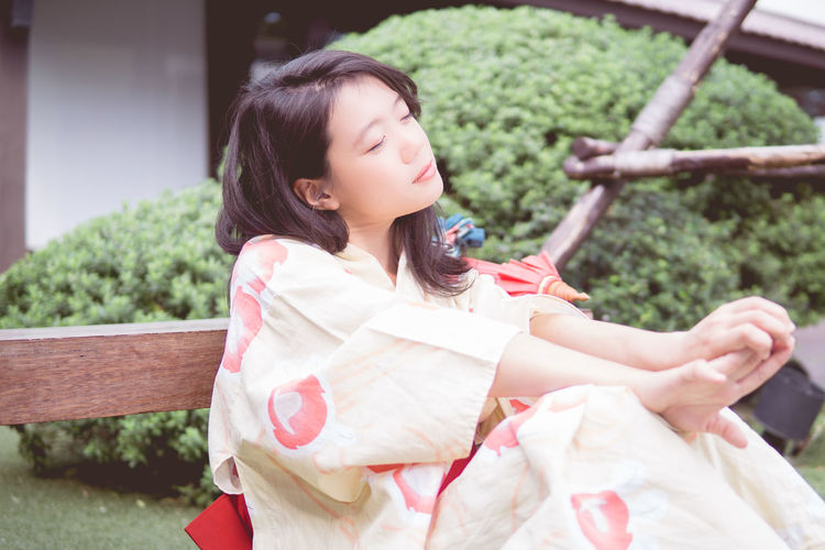 Beautiful Woman Black Hair Day Leisure Activity Lifestyles Medium-length Hair Nature One Person Outdoors Park - Man Made Space People Real People Relaxation Sitting Tree Young Adult Young Women