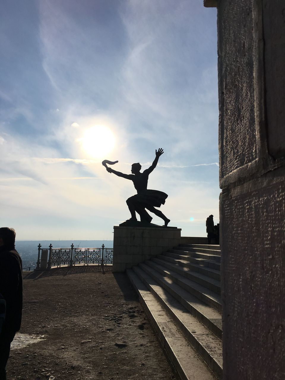 sky, silhouette, full length, men, real people, sunset, statue, lifestyles, skill, cloud - sky, sculpture, built structure, day, jumping, energetic, outdoors, architecture, handstand, water, stunt, nature, one person, people