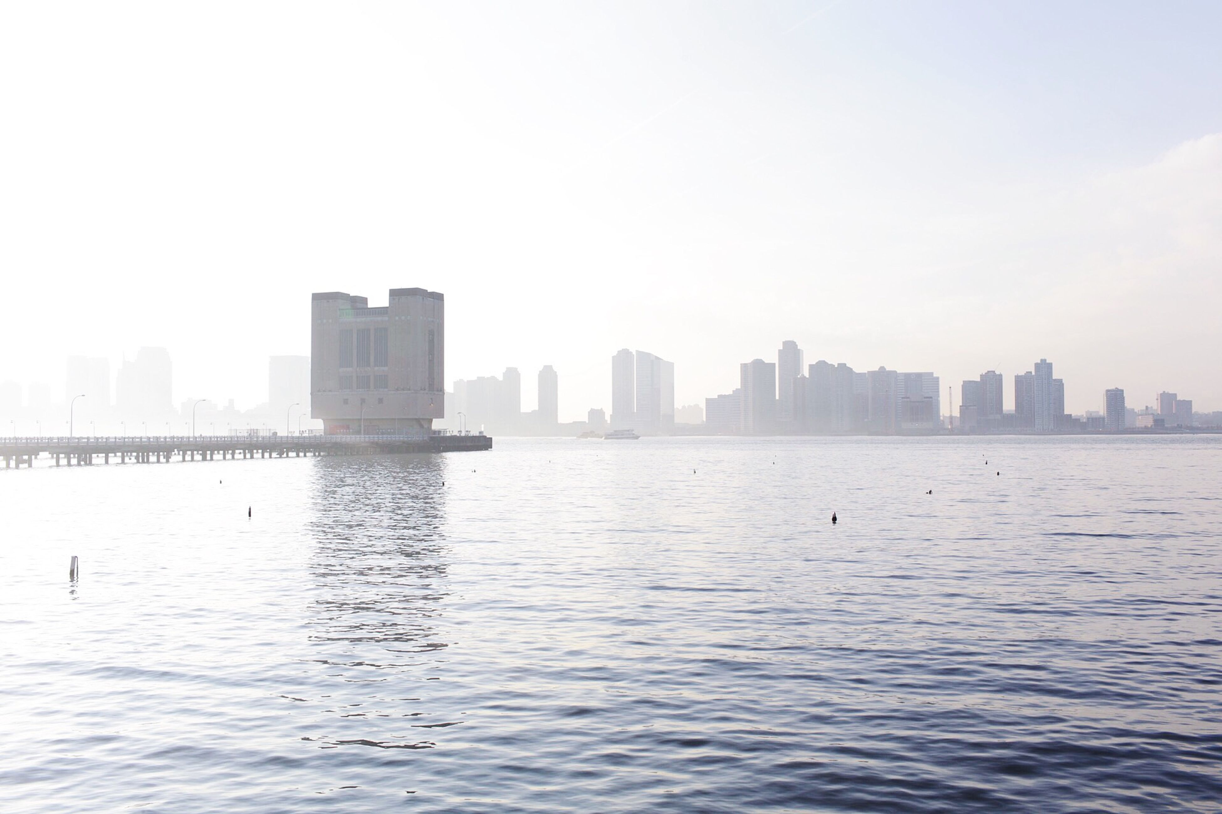 building exterior, city, water, waterfront, architecture, built structure, cityscape, skyscraper, clear sky, urban skyline, copy space, river, sea, rippled, skyline, tower, sky, mid distance, office building, tall - high
