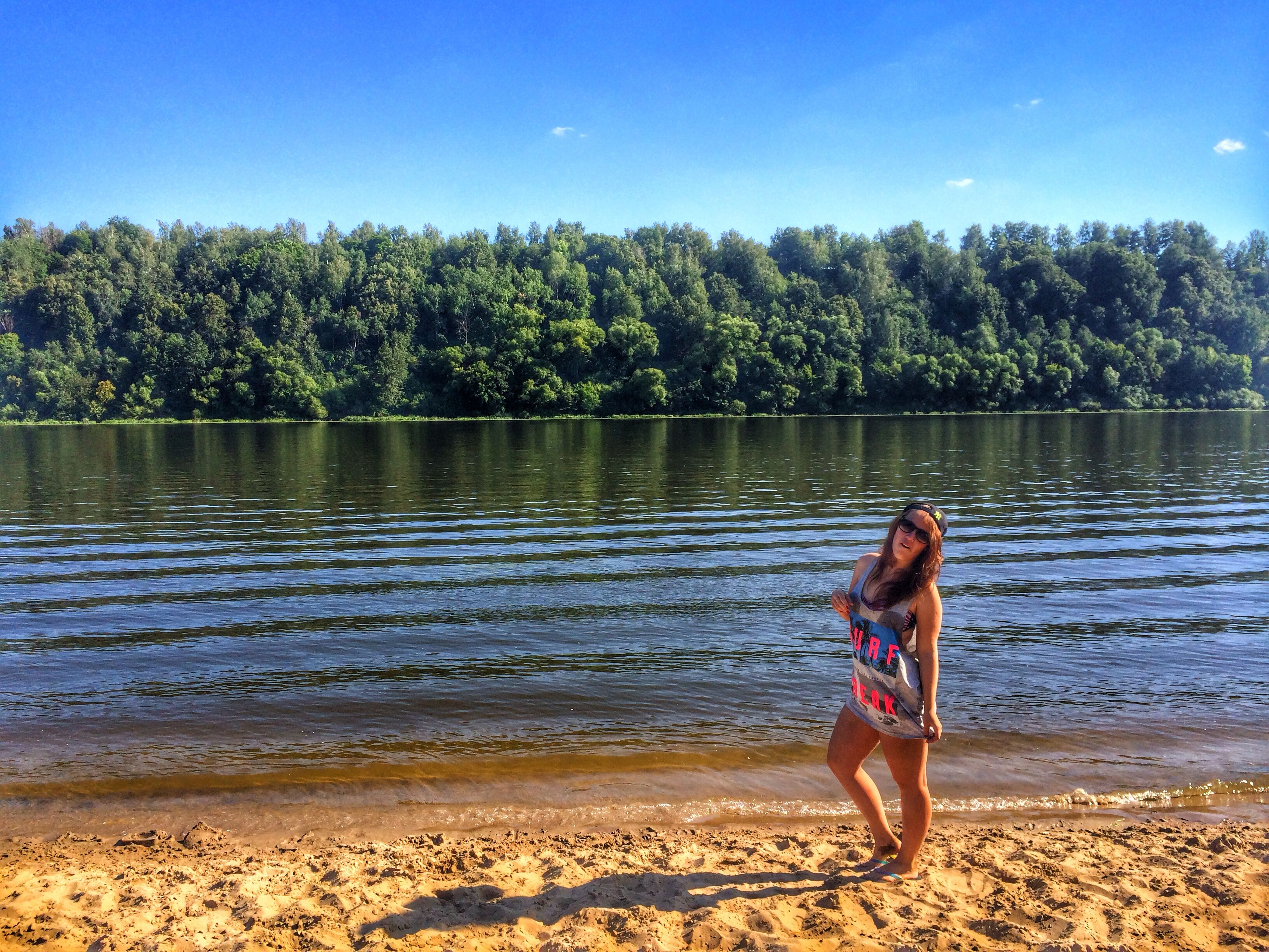 water, tree, lifestyles, leisure activity, casual clothing, full length, tranquility, standing, rear view, nature, beauty in nature, lake, beach, tranquil scene, young adult, sunlight, day, shore