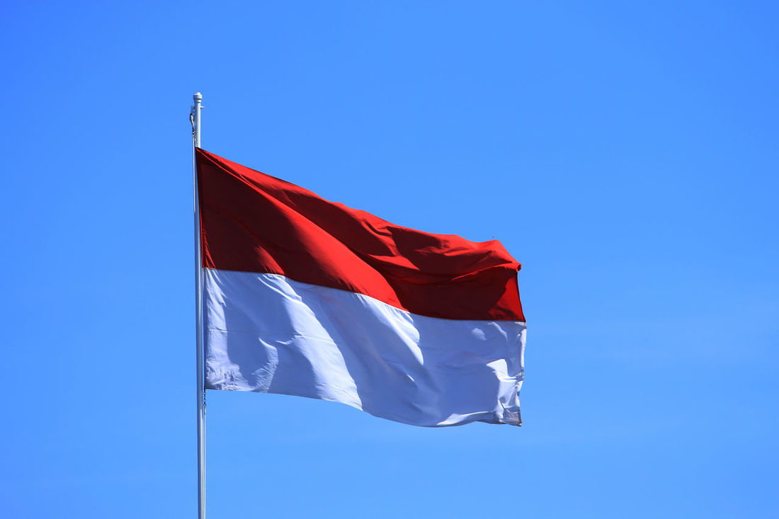 Indonesia flag flying high Blue Blue Sky Clear Sky Day Flag Flying High INDONESIA Indonesia Flag Low Angle View No People Outdoors Patriotism Patriotism Red Red Red And White Symbol White