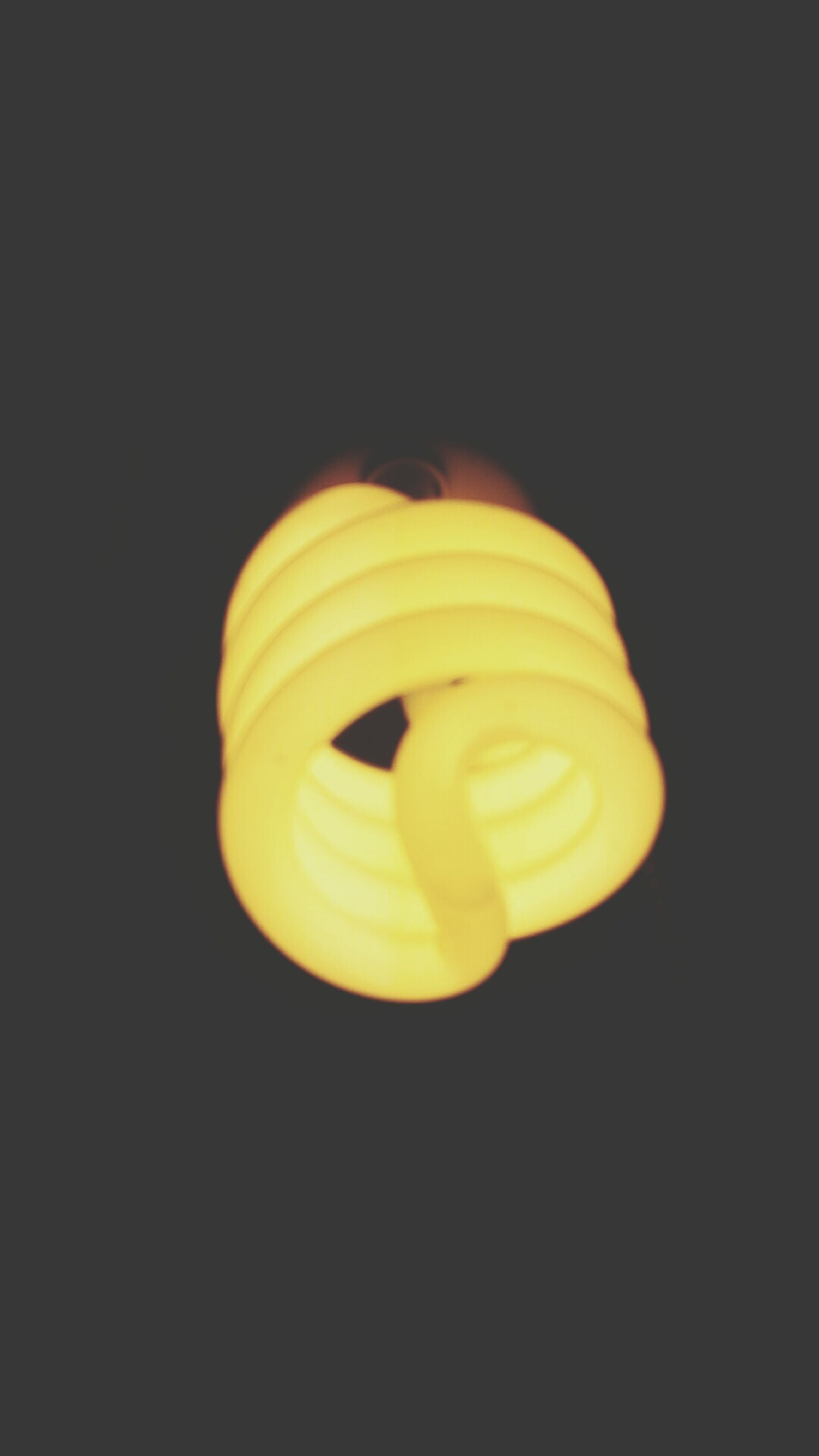 studio shot, black background, copy space, indoors, creativity, close-up, art and craft, still life, art, illuminated, yellow, single object, pattern, circle, shape, no people, design, cut out, orange color, spiral