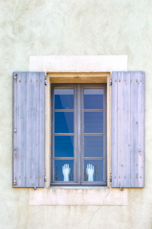 Open rustic wooden light blue shutters at window with hands up in Carcassonne, Frane Architecture Building Exterior Built Structure Close-up Corners Decoration Decorations Door Edges Elevation Hands Hands Up House Light Blue Minimalistic Open Outdoors Plant Rectangle Shutters Single Vintage Wall Window Wood - Material