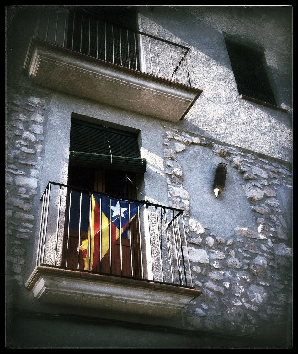 The Catalan flag of independence hangs from a balcony in the traditional town of Mora d'Ebre, with an artillery shell mounted on the wall, Catalonia, Spain. Architecture Bomb Shell Building Built Structure Exterior IPhoneography No People Outdoors SPAIN Travel Travel Destinations Travel Photography Traveling