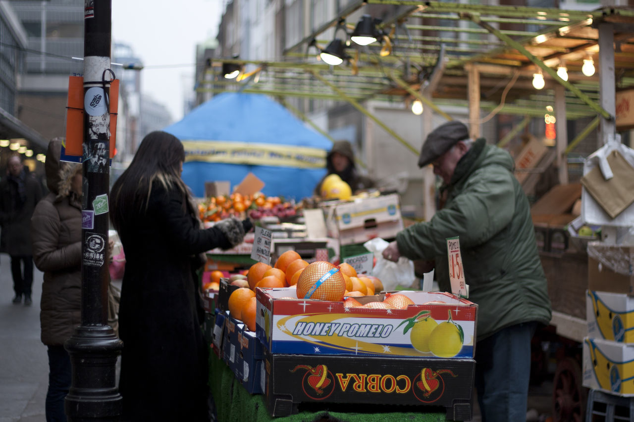 market, market stall, food, food and drink, real people, fruit, healthy eating, freshness, vegetable, standing, men, outdoors, retail, women, day, price tag, occupation, groceries, people