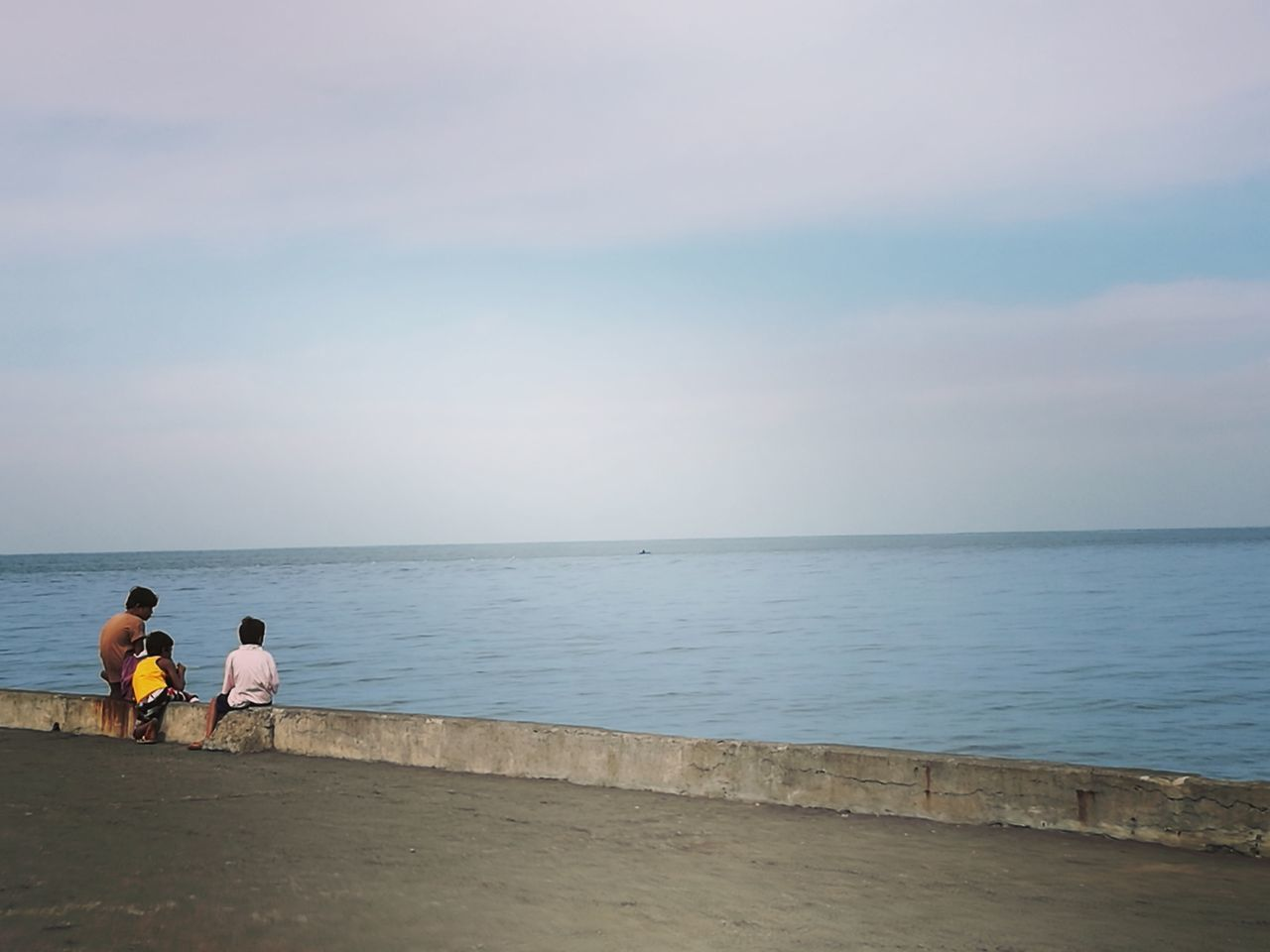 sea, horizon over water, water, real people, rear view, nature, scenics, beauty in nature, togetherness, two people, tranquil scene, leisure activity, beach, sky, outdoors, men, tranquility, sitting, lifestyles, vacations, women, day, full length, fishing pole, people
