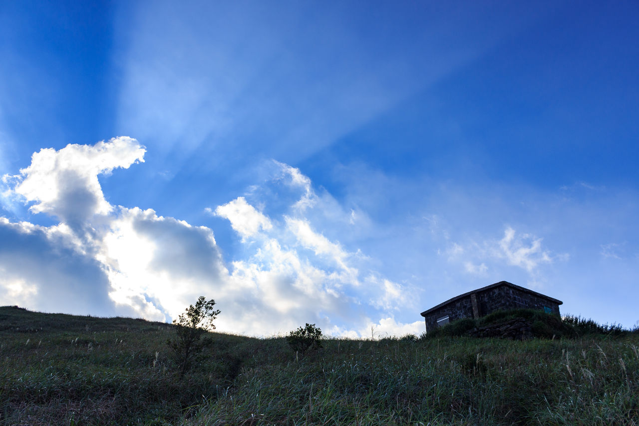 sky, built structure, tranquil scene, tranquility, house, day, outdoors, no people, scenics, landscape, nature, architecture, cloud - sky, field, blue, building exterior, grass, beauty in nature, mountain
