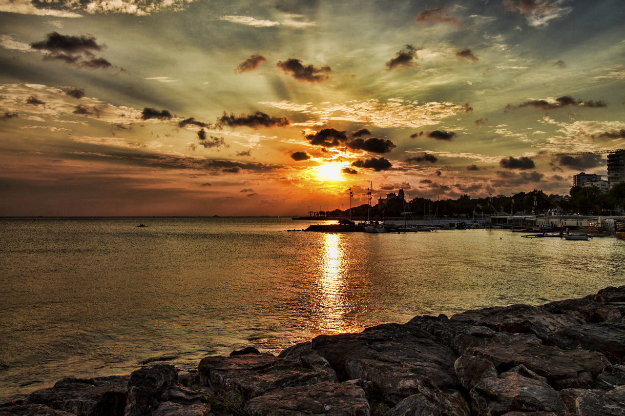 sunset, sky, cloud - sky, scenics, water, beauty in nature, sea, sun, tranquil scene, nature, reflection, tranquility, no people, dramatic sky, outdoors, rock - object, horizon over water, silhouette, beach, travel destinations, tree, day