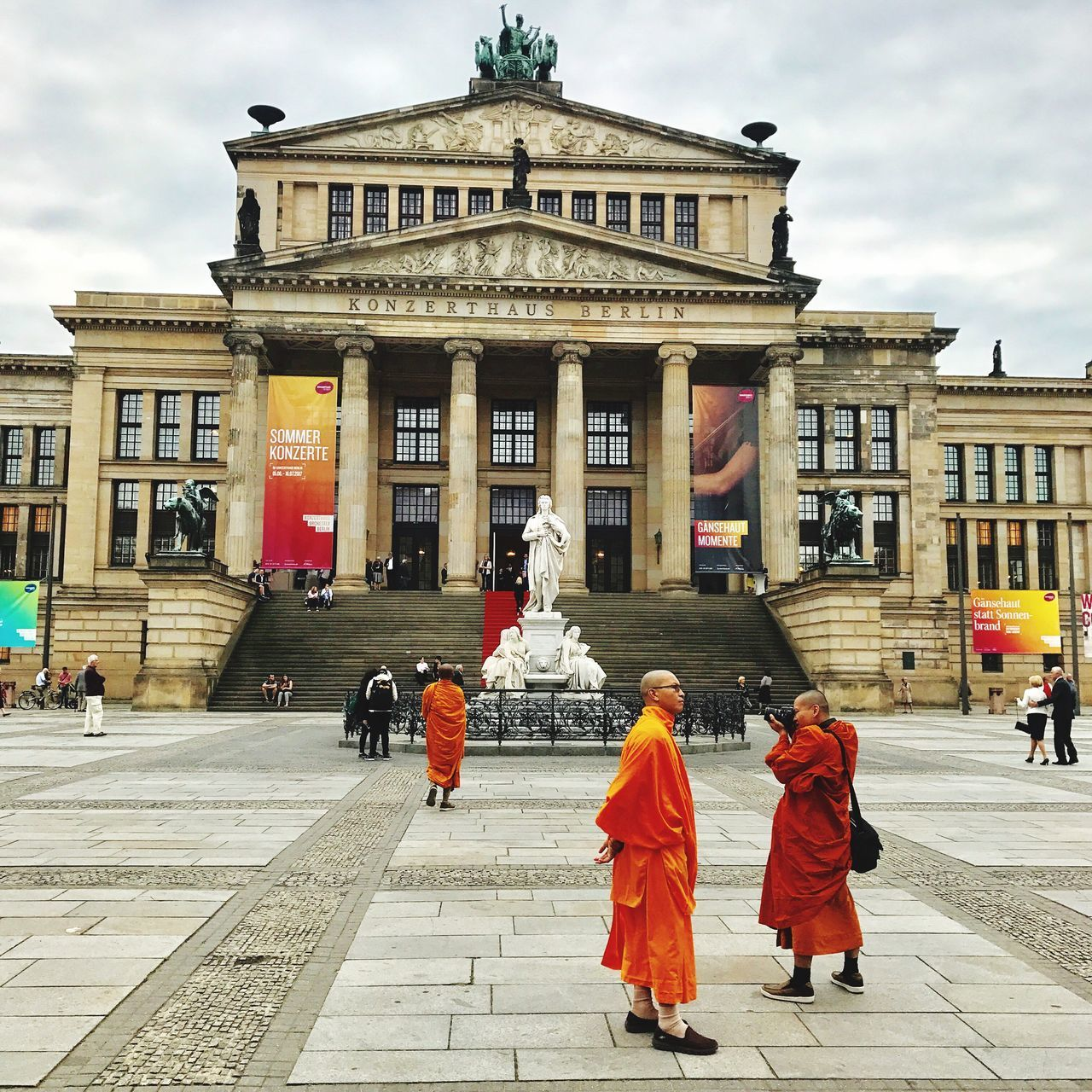 architecture, built structure, building exterior, real people, statue, architectural column, travel destinations, women, sculpture, sky, men, history, outdoors, facade, cloud - sky, large group of people, day, city, lifestyles, adult, people