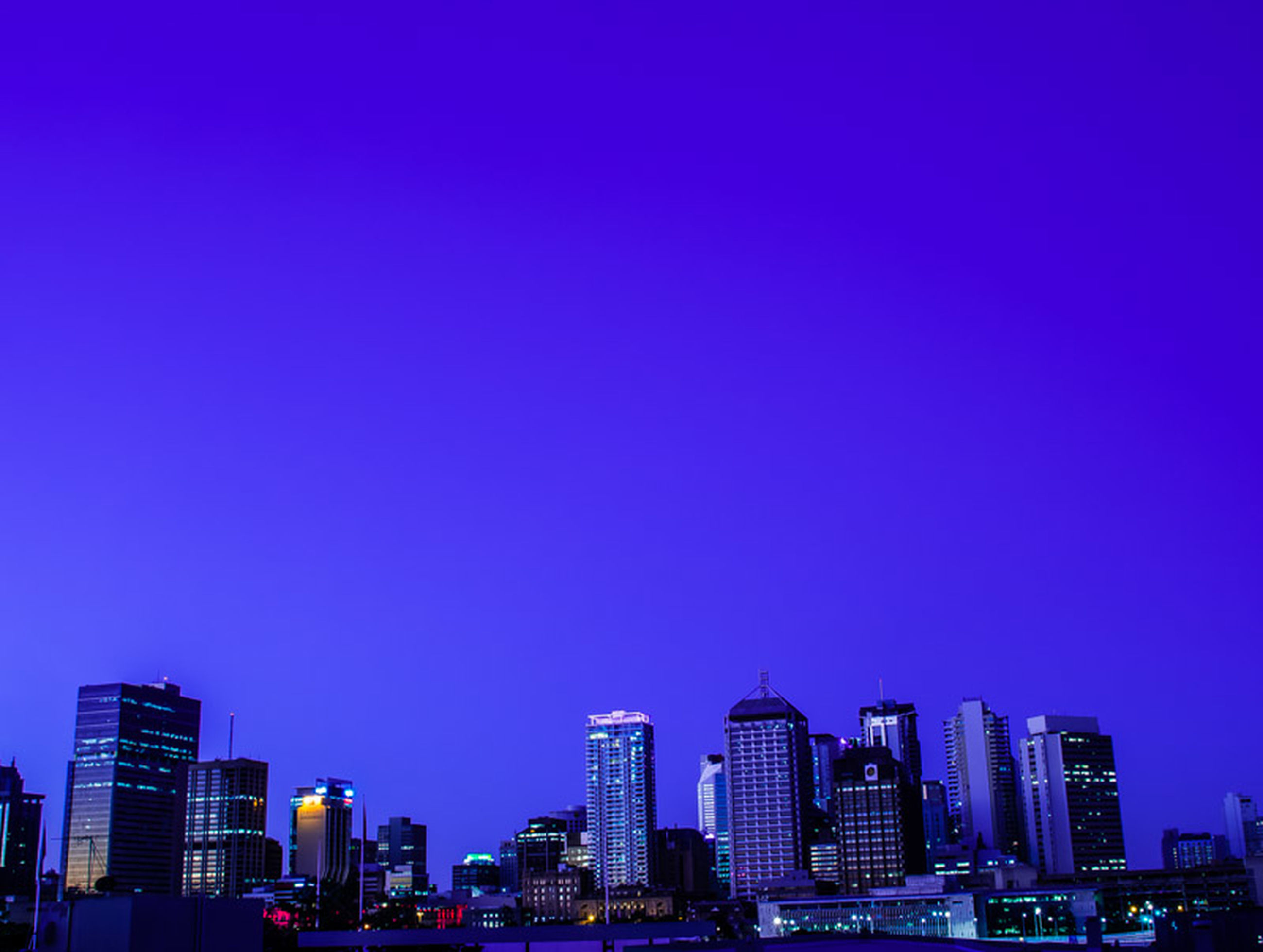 building exterior, city, architecture, clear sky, built structure, copy space, blue, skyscraper, cityscape, illuminated, night, modern, tall - high, urban skyline, office building, tower, city life, low angle view, outdoors, financial district