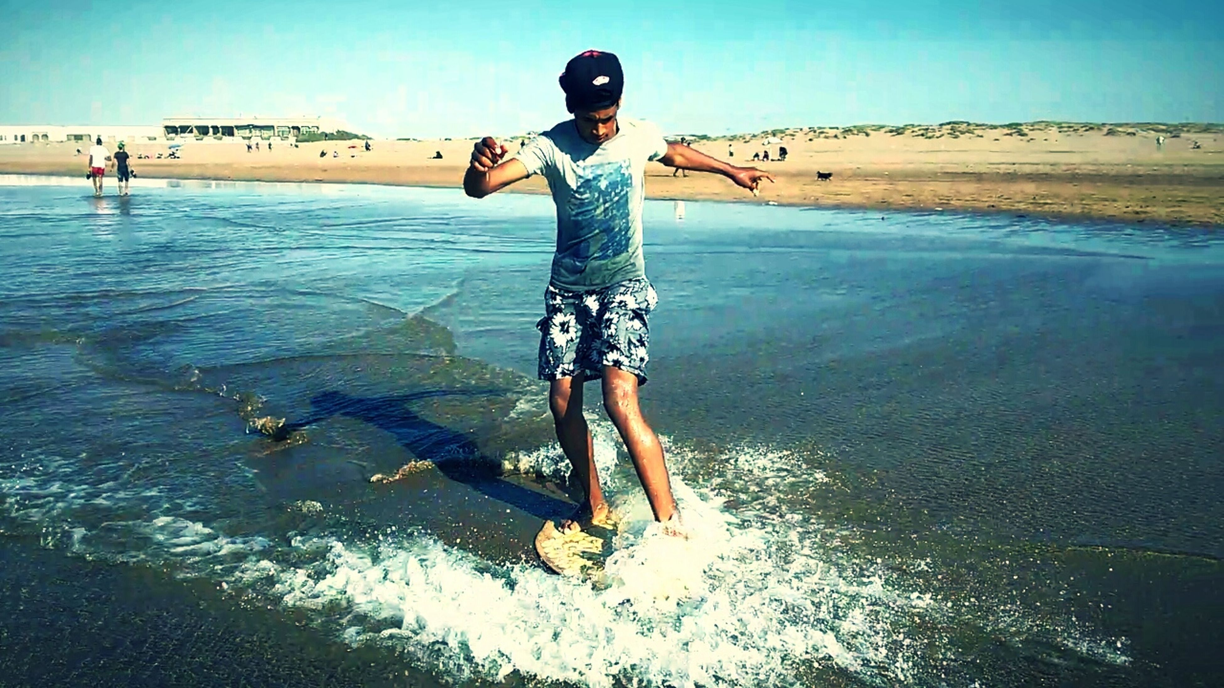 water, full length, lifestyles, leisure activity, front view, casual clothing, portrait, vacations, fun, enjoyment, arms outstretched, sky, jumping, day, nature, outdoors, tranquility