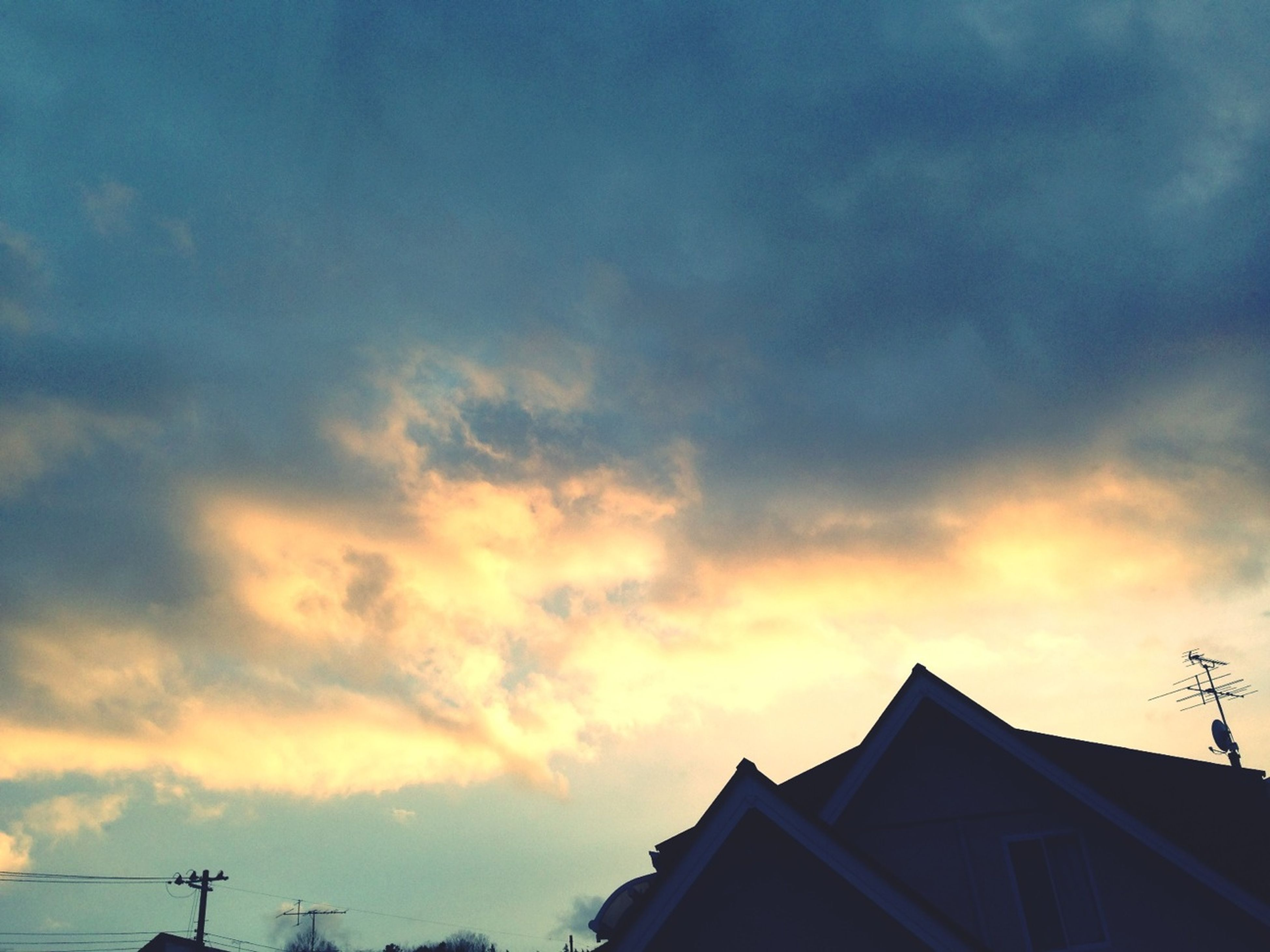 building exterior, architecture, built structure, low angle view, sky, sunset, cloud - sky, cloudy, high section, house, silhouette, cloud, orange color, residential structure, roof, building, residential building, outdoors, weather, nature