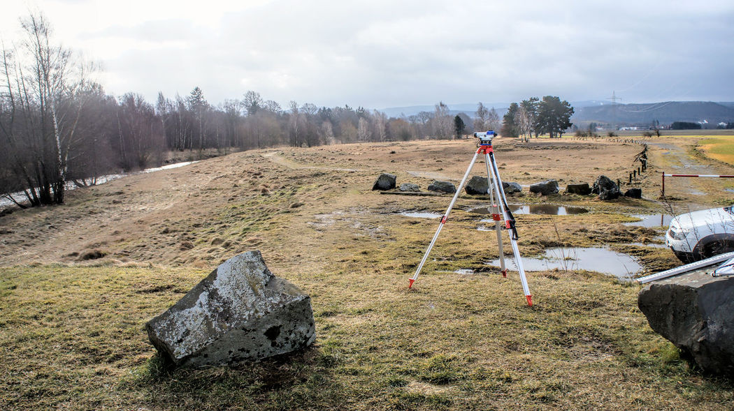 """Surveying of slag heaps on the river """"Innerste"""" near Bredelem, Goslar, Harz Mountains Contamination Beauty In Nature Cloud - Sky Cold Temperature Day Deposit Field Heap Landscape Level Leveling Metallurgy Nature Outdoors Poisonous Rangefinder Real People Sky Slag Slag Heap Terrain Tree Tripod"""