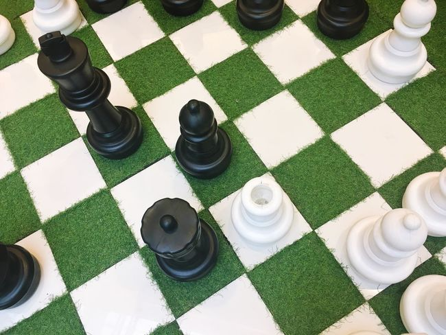 Chess Chessboard Chesspieces Chess Piece Chess Board Chess Game Chess Set Chess Pieces High Angle View Low Section Grass Person Footwear Green Medium Group Of Objects Green Color Grassy Colors And Patterns