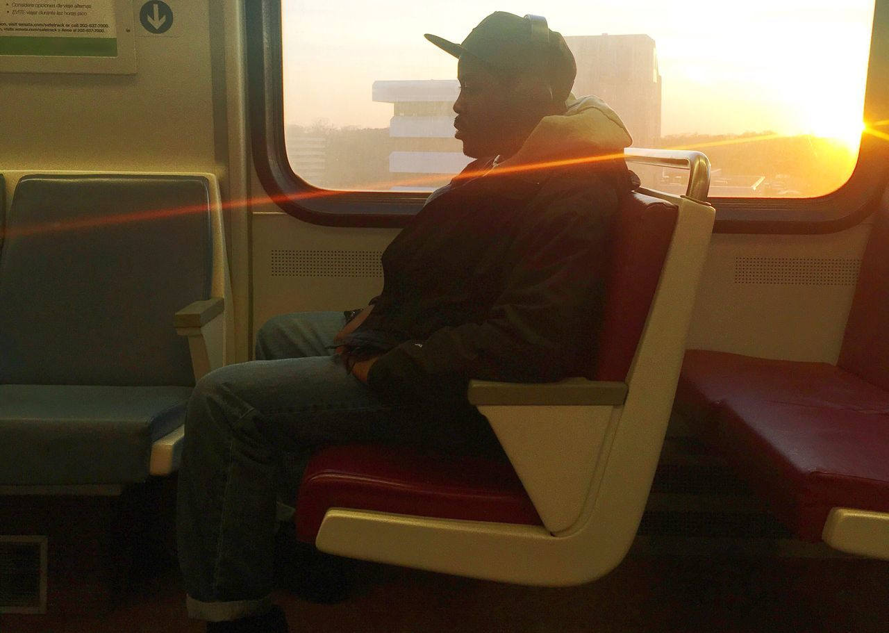 Side View Of Young Man Sitting In Train During Sunset
