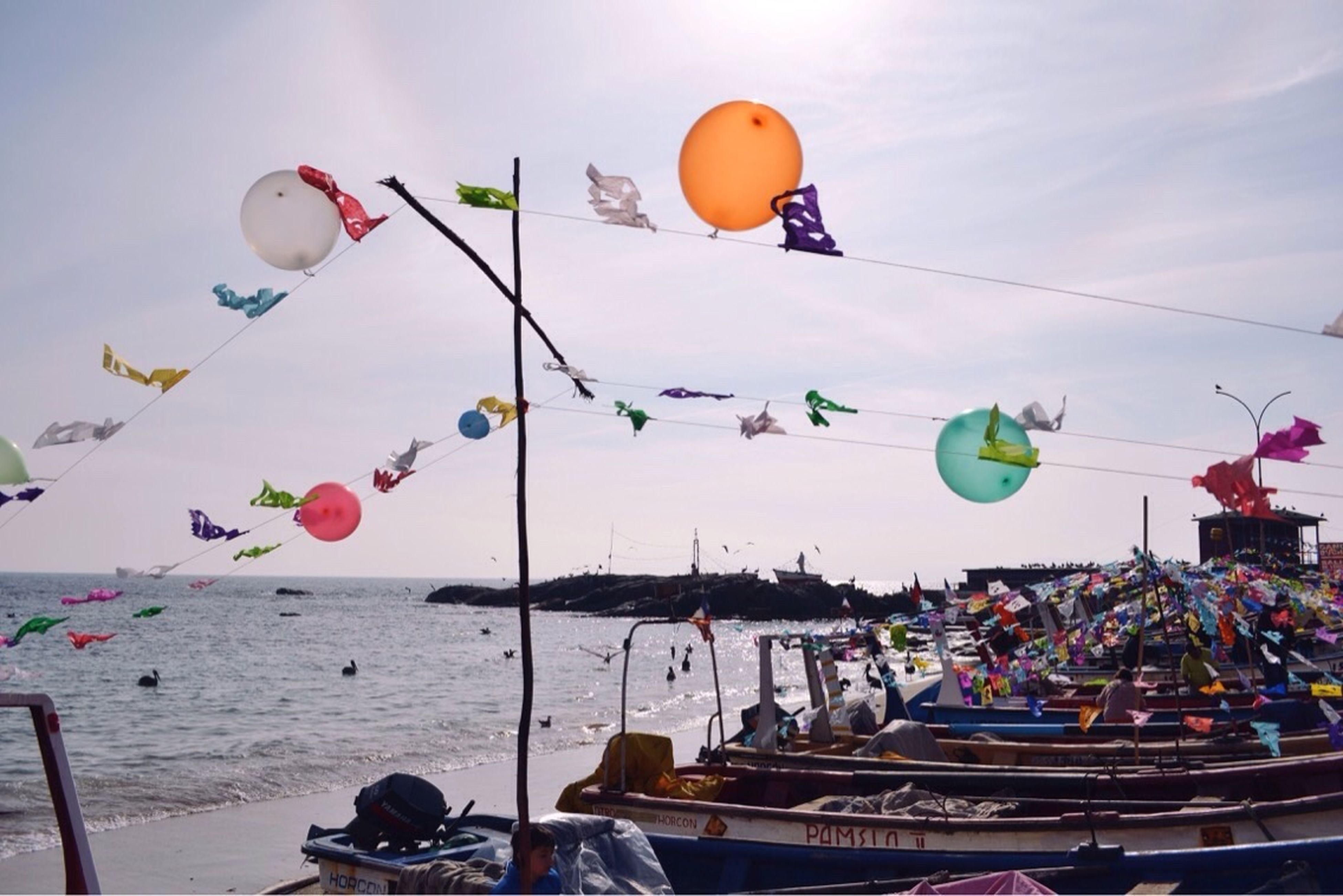 real people, outdoors, sky, balloon, multi colored, sea, day, celebration, men, large group of people, nature, people