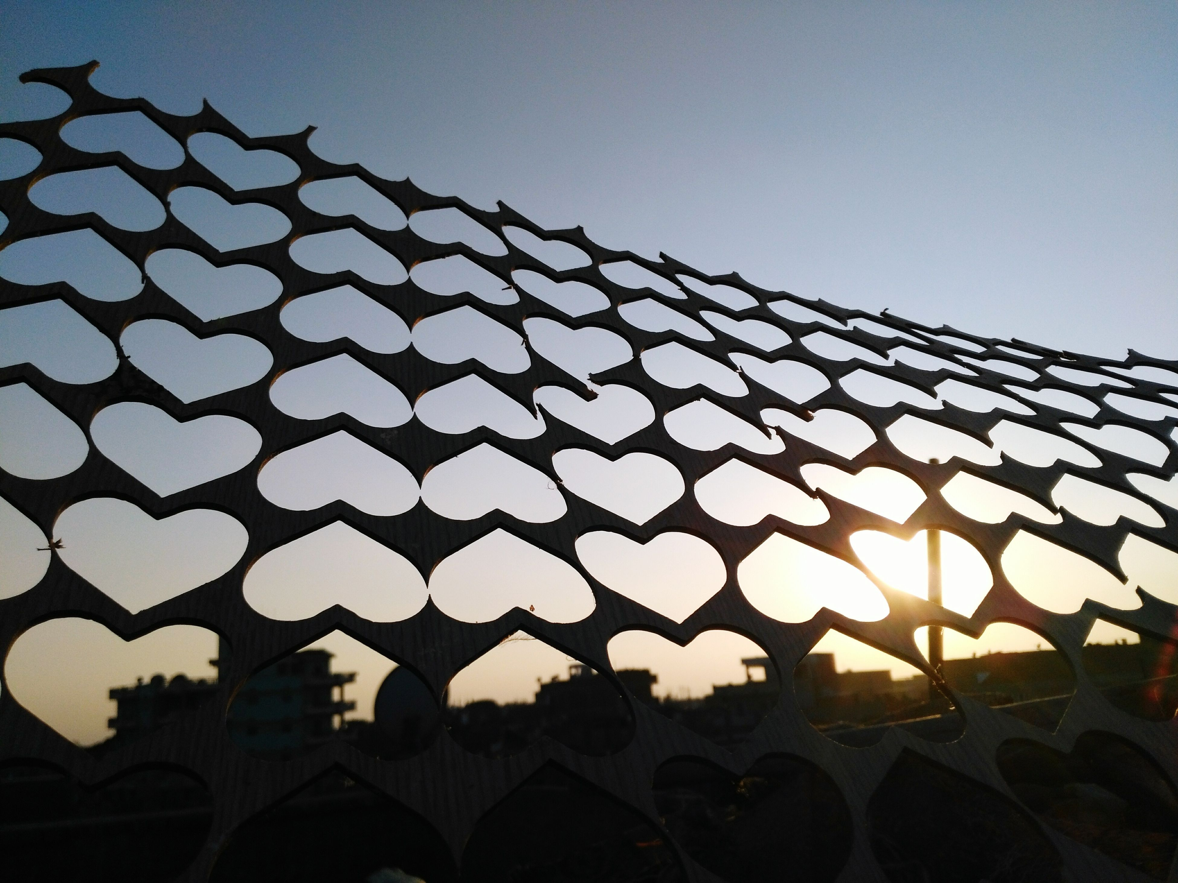 protection, safety, fence, clear sky, silhouette, pattern, architecture, low angle view, sky, building exterior, outdoors, chainlink fence, architectural feature, geometric shape, no people, arrangement