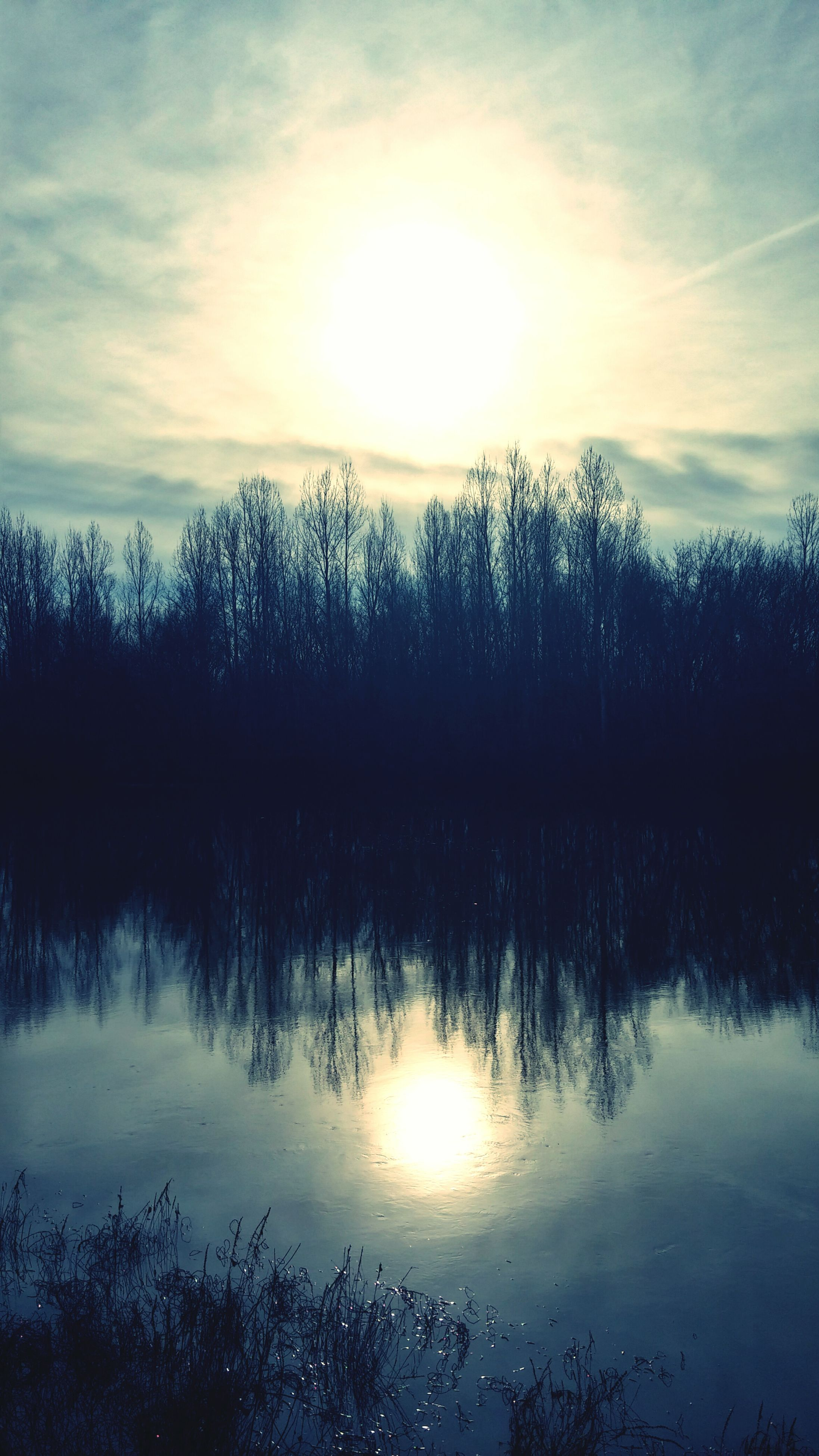 reflection, water, tranquil scene, lake, tranquility, scenics, tree, sky, beauty in nature, sunset, sun, nature, silhouette, cloud - sky, idyllic, waterfront, sunlight, cloud, outdoors, bare tree