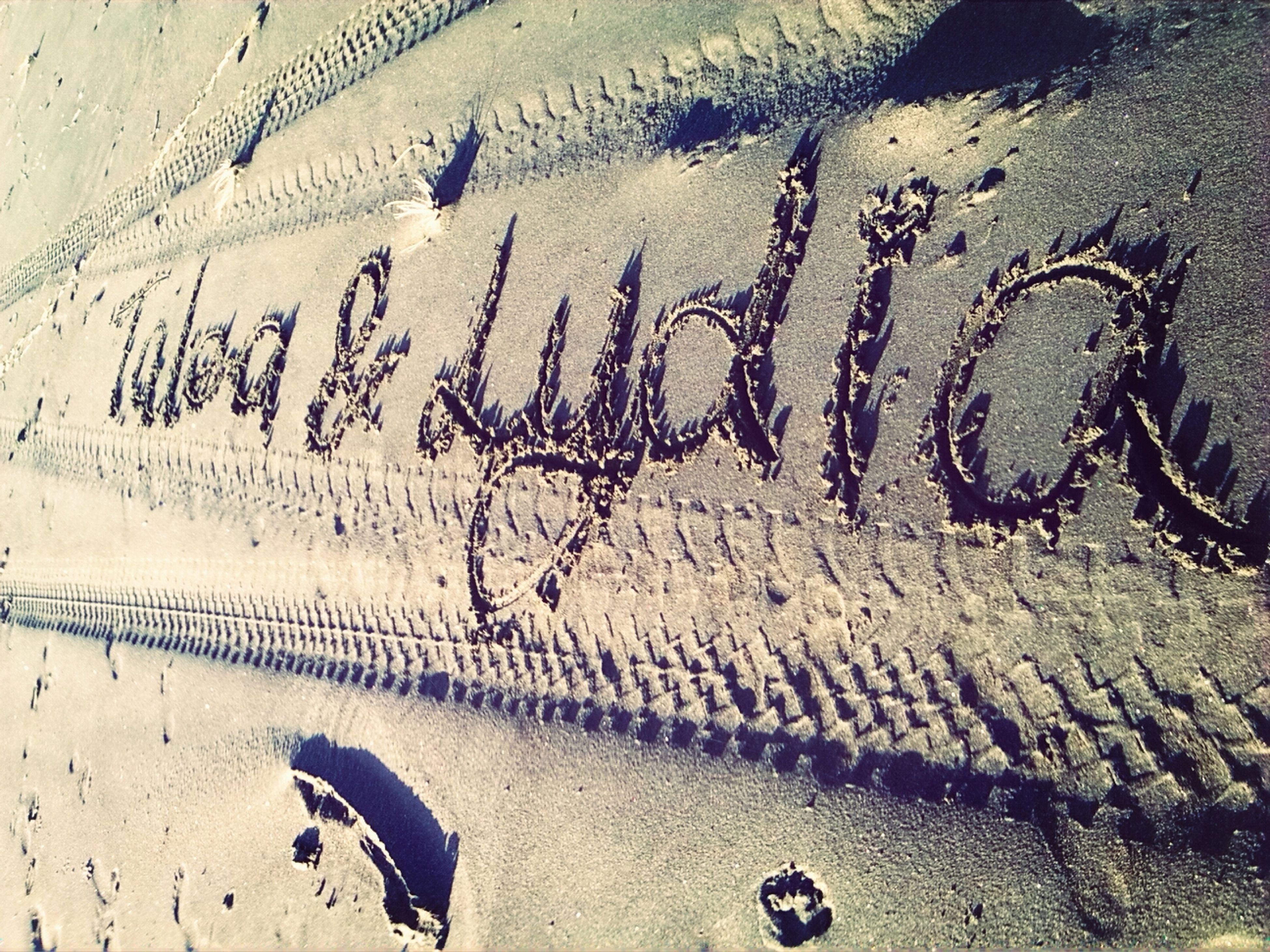 text, sand, western script, graffiti, wall - building feature, communication, beach, high angle view, footprint, day, textured, outdoors, wall, shadow, sunlight, no people, art, capital letter, street, creativity