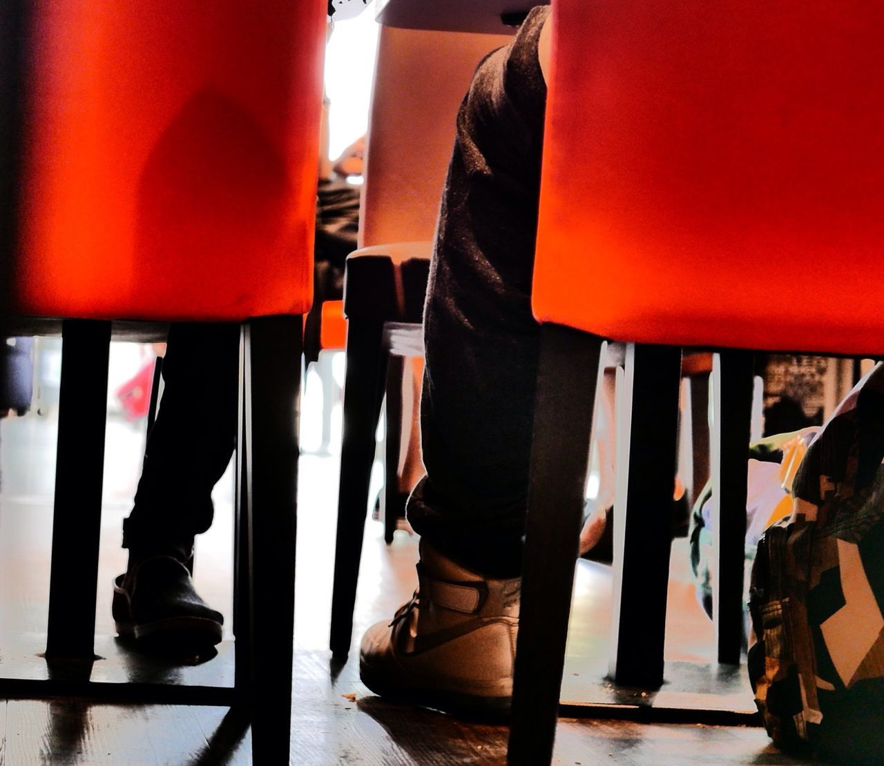 Low Section Of People Sitting At Restaurant On Red Chairs