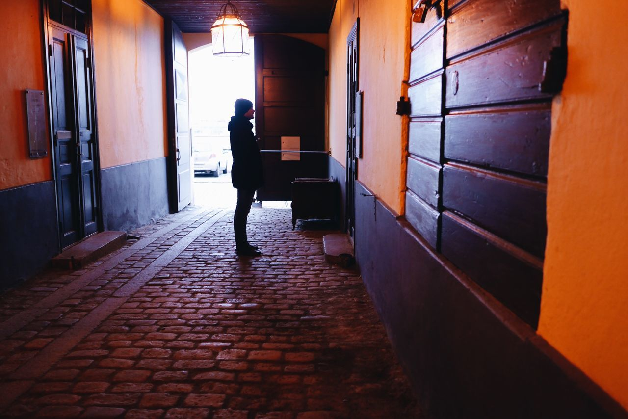 Man in an old gateway Wooden Post Wooden Door Exterior View Exterior View Old Buildings Silhouette Full Length One Person Real People Walking Lifestyles The Way Forward Women Men Architecture Adult Adults Only People Standing Day