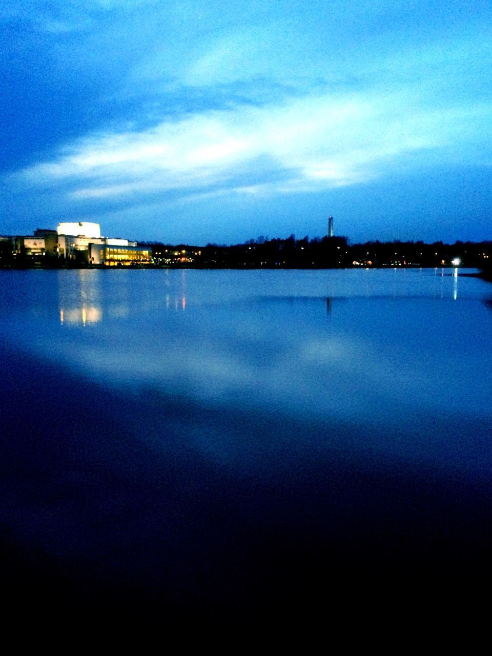 water, reflection, sky, architecture, illuminated, built structure, dusk, waterfront, cloud - sky, no people, sea, blue, nature, tranquil scene, building exterior, outdoors, night, beauty in nature, scenics, city