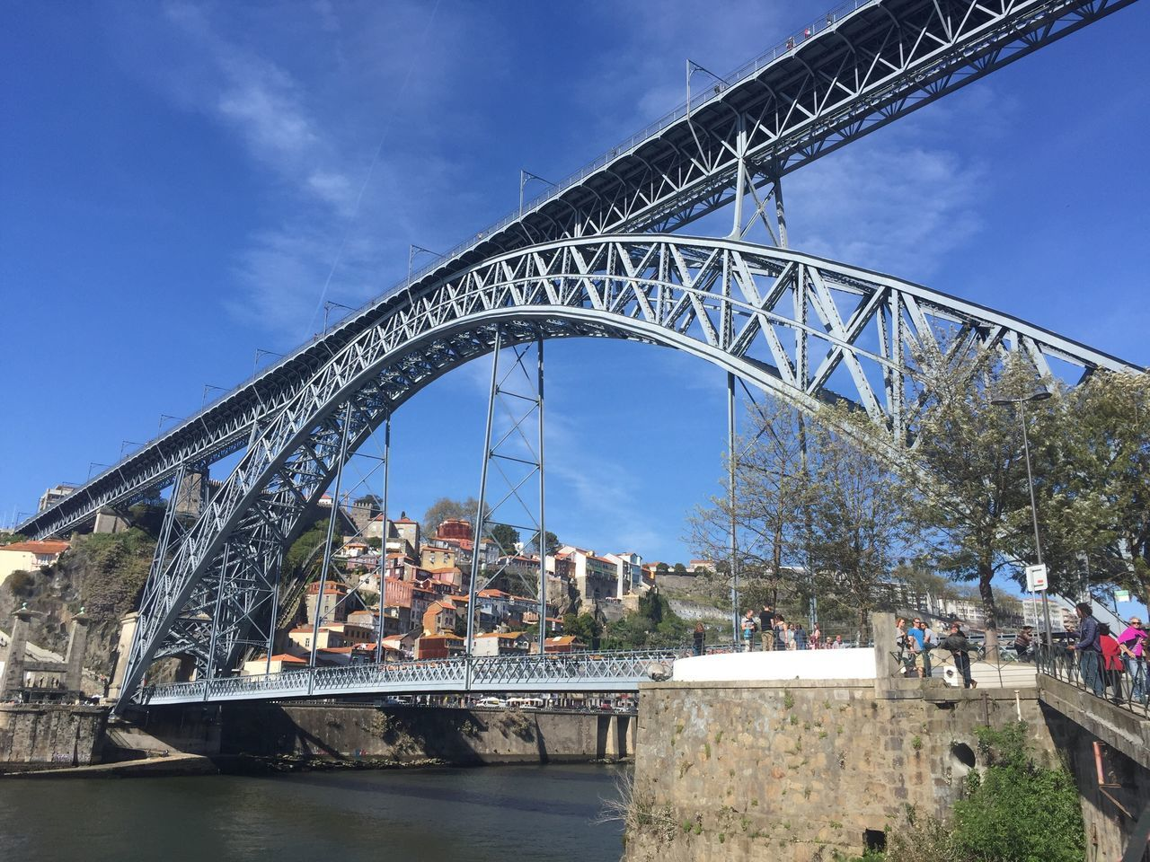 bridge - man made structure, built structure, architecture, engineering, connection, sky, outdoors, tourism, day, travel destinations, tree, travel, water, low angle view, cloud - sky, large group of people, building exterior, nature, city, chain bridge, people