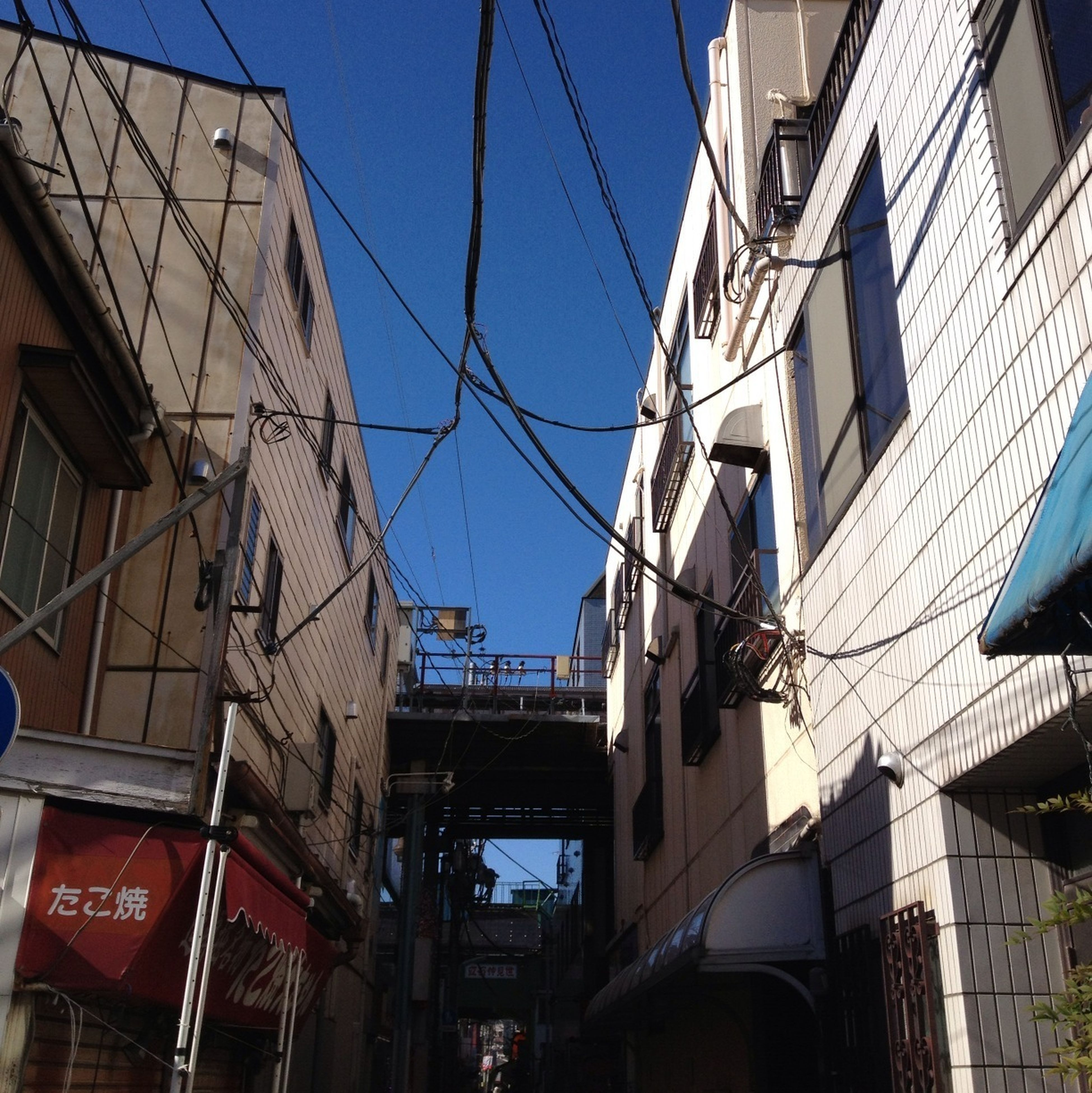 architecture, built structure, building exterior, low angle view, city, building, clear sky, residential structure, residential building, blue, window, cable, connection, day, outdoors, power line, no people, sky, sunlight, modern