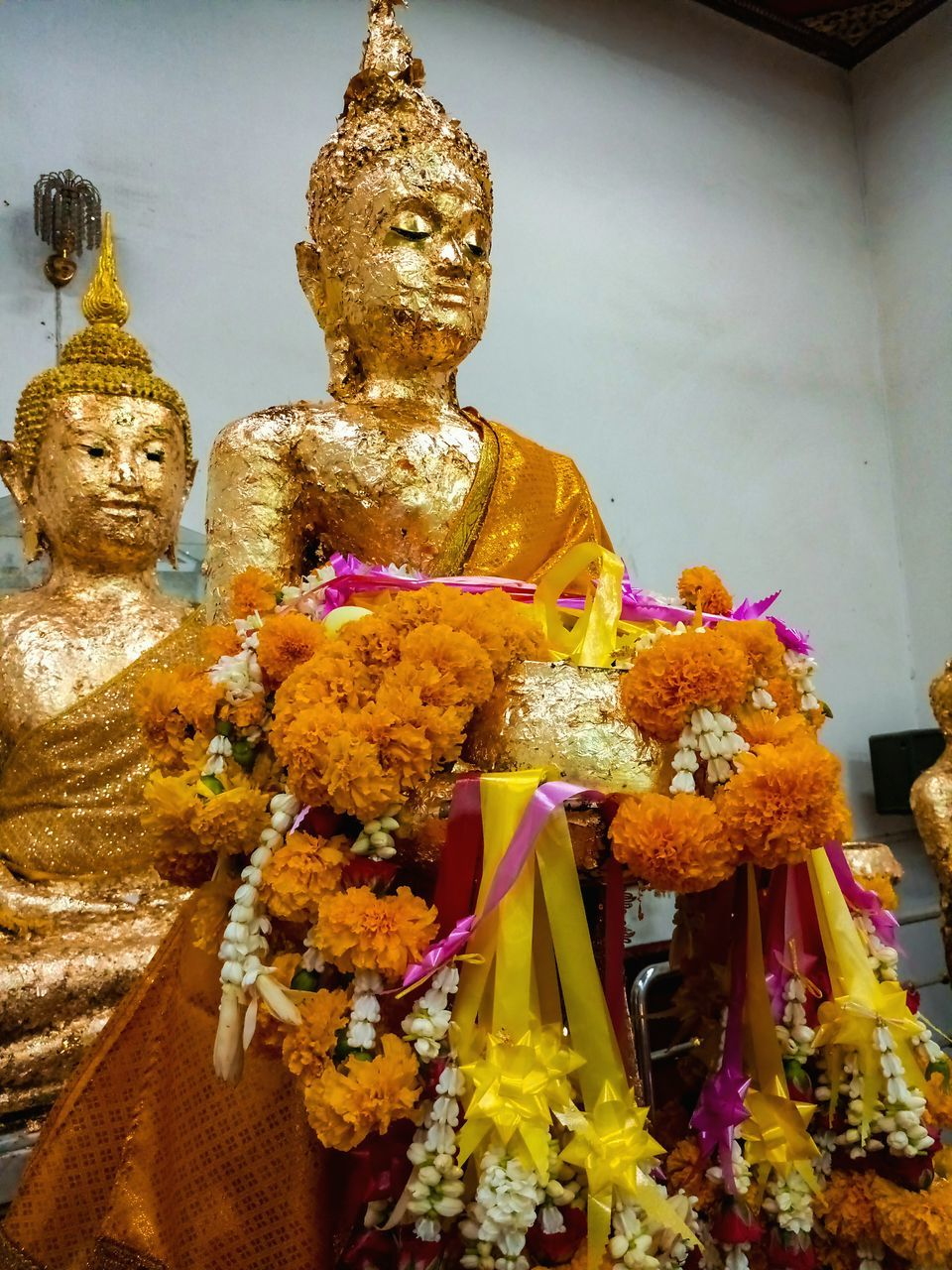 religion, statue, spirituality, sculpture, male likeness, human representation, place of worship, art and craft, garland, idol, no people, indoors, flower, close-up, day