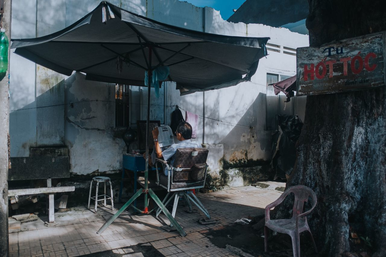 The old man is resting at the barbershop on the street, Vietnamese