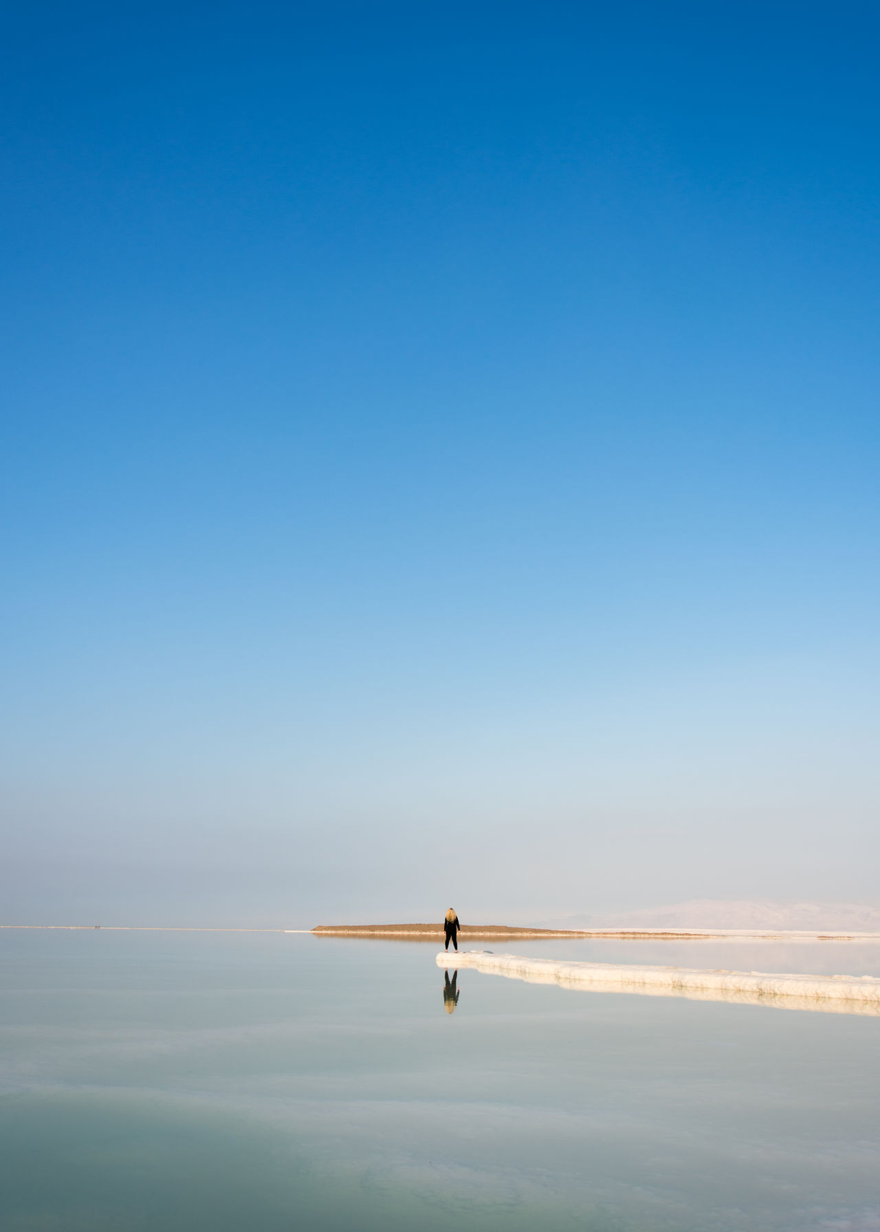 Minimalist Shooting Day At The Lowest Place On Earth -416 meters below sea level -Deadsea Israel Adventure Beauty In Nature Blue Clear Sky Deadsea Finding New Frontiers Golden Hour Israel Minimal Minimalism Minimalist Minimalobsession One Person Outdoors Reflection Reflection Reflections Salt Saltwater Tranquil Scene Tranquility Water EyeEm Team Rear View Getty X EyeEm Traveling Home For The Holidays