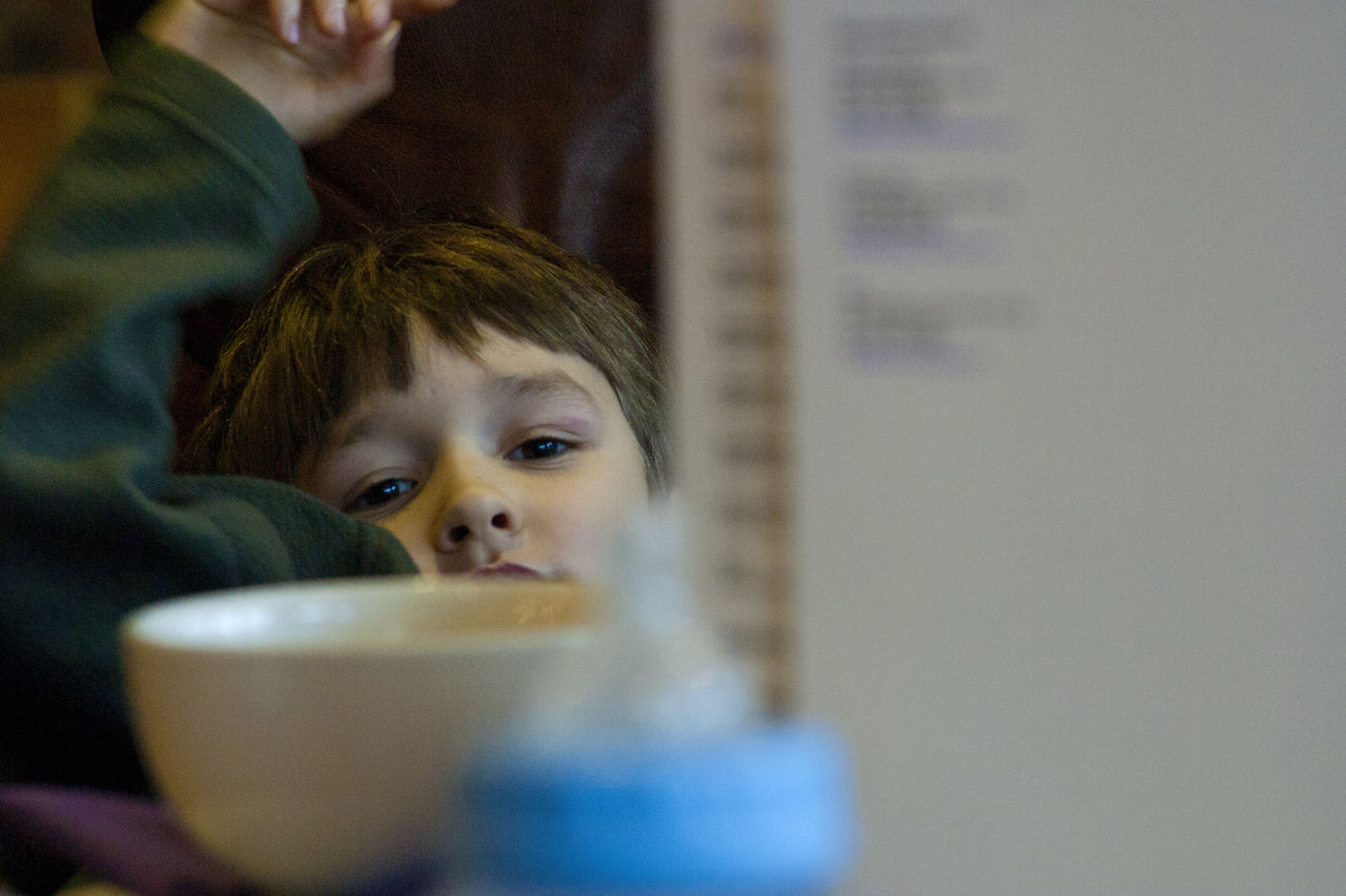 Bored Boredom Boy Boys Cafe Childhood Eating Out Elementary Age Eyes Eyes Watching You Food And Drink Indoors  Lifestyles Portrait Real People Selective Focus Shallow Depth Of Field