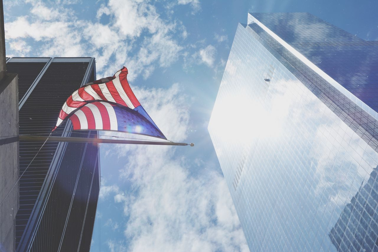 Low Angle View Of American Flag And Buildings Against Cloudy Sky